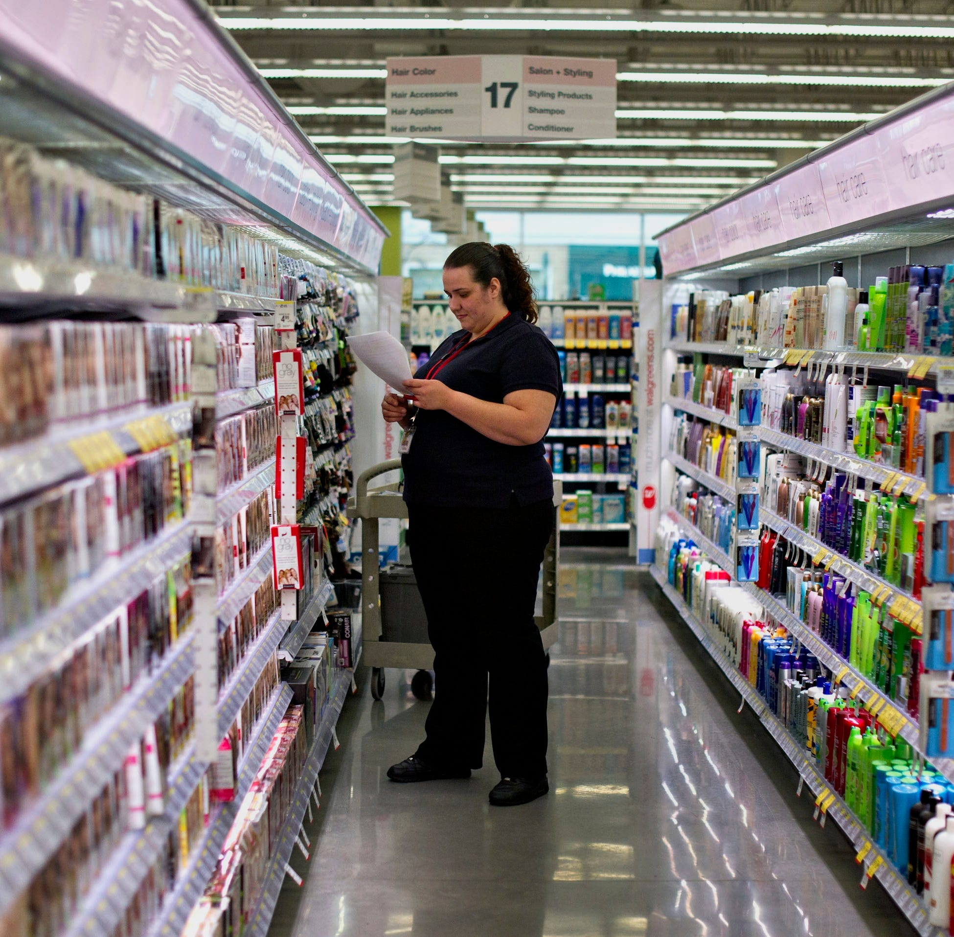 Employee Carrie Garza, a senior beauty advisor, looks over a merchandising list while adding new products to a dislpay at a Walgreen Co.