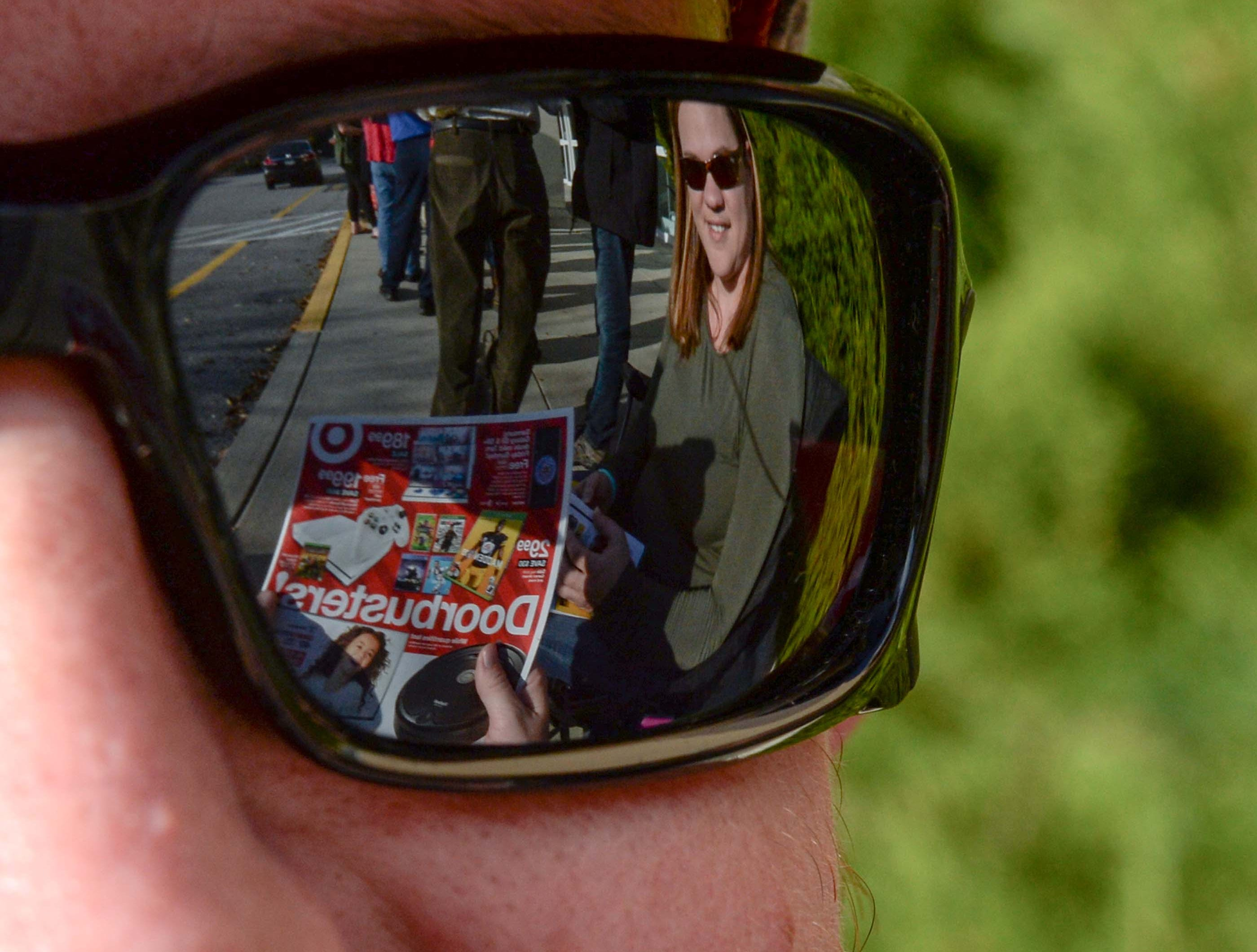 Kevin Crisco and Tiffany Pake of Anderson both look at newspaper ads while waiting in line for doors to open for Black Friday sales at Kohl's in Anderson on Thanksgiving Day, Thursday, November 22, 2018.