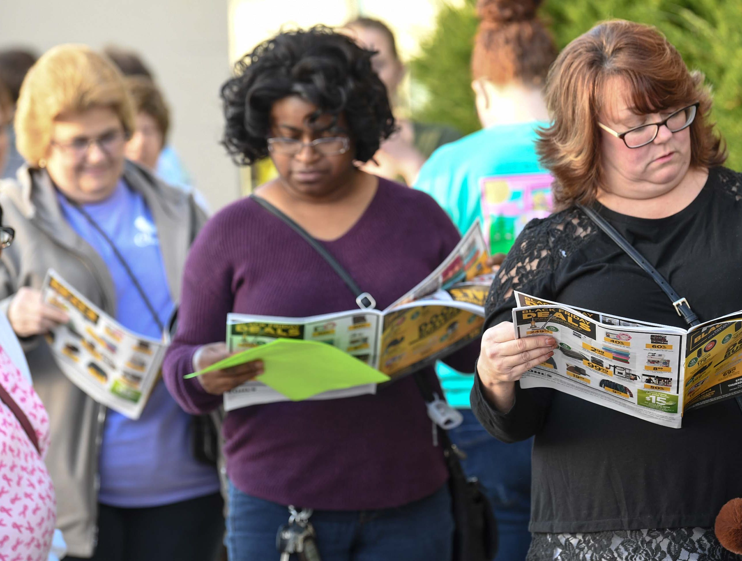 Patti Hipps, left, Sandy Glaze, and Leann Rumsey look at advertisement papers while waiting in line for doors to open for Black Friday sales at Kohl's in Anderson on Thanksgiving Day, Thursday, November 22, 2018.