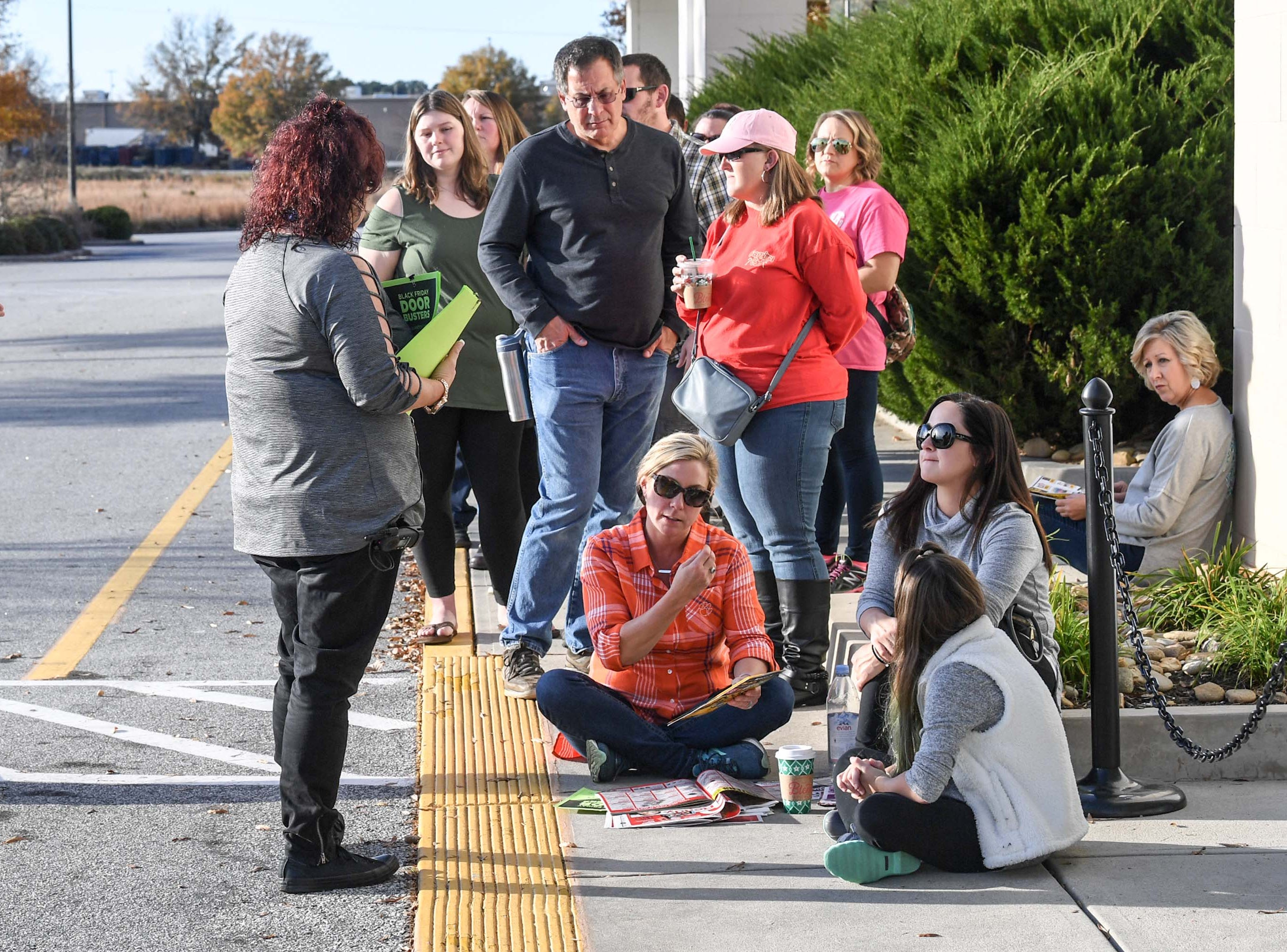 Shannon Roberts, left, a Kohl's area manager, answers a question from first in line customer Sunny Davis, with Victoria Bonnette, and Lilah Bonnette, while waiting in line for doors to open for Black Friday sales at Kohl's in Anderson on Thanksgiving Day, Thursday, November 22, 2018.