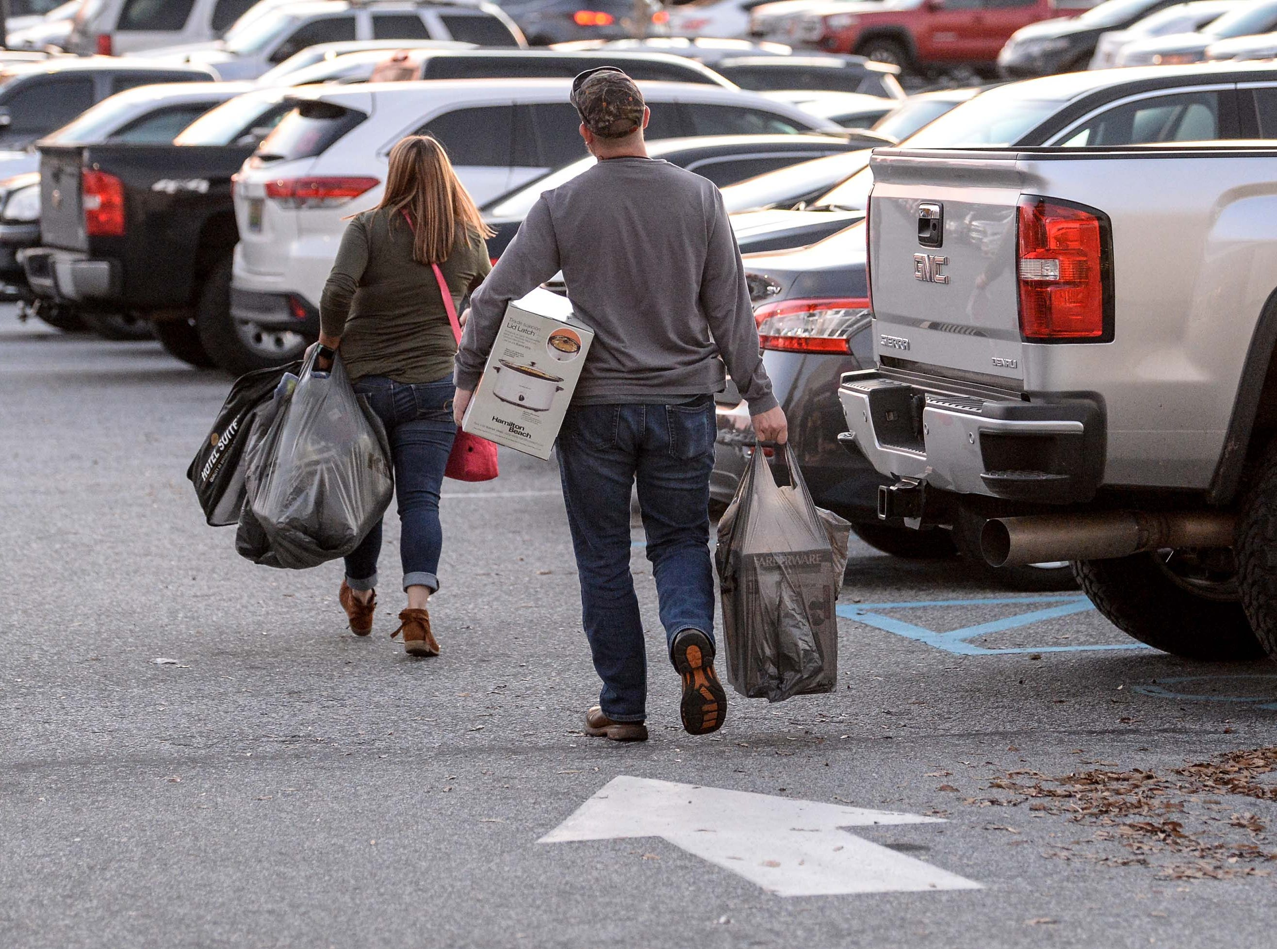 Tiffany Pake, left, of Anderson and Kevin Crisco leave Kohl's in Anderson with sale items on Thanksgiving Day, Thursday, November 22, 2018.