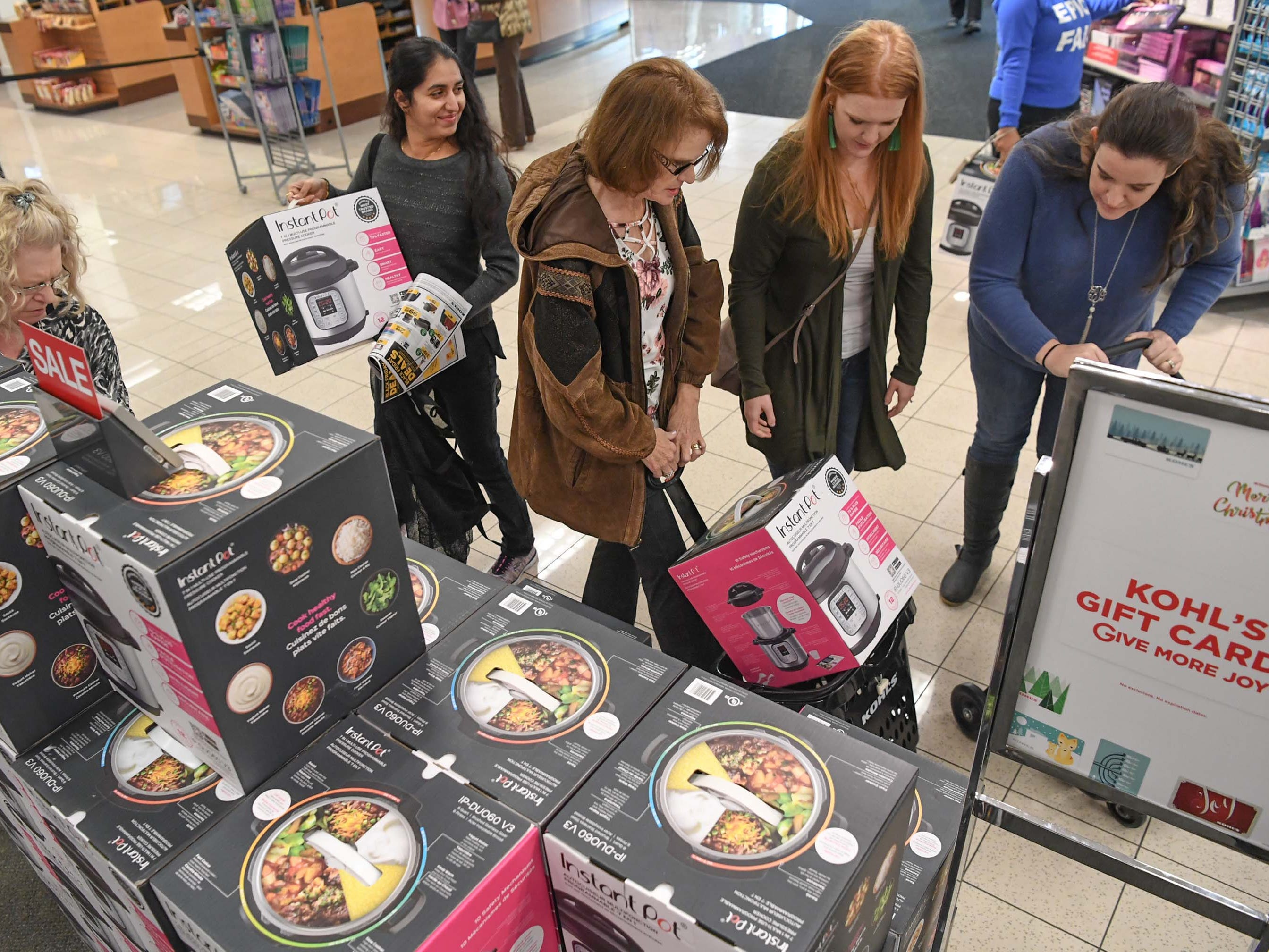Shivangi Raval, left, of Anderson picks up a sale item pressure cooker during Black Friday sales at Kohl's in Anderson on Thanksgiving Day, Thursday, November 22, 2018.