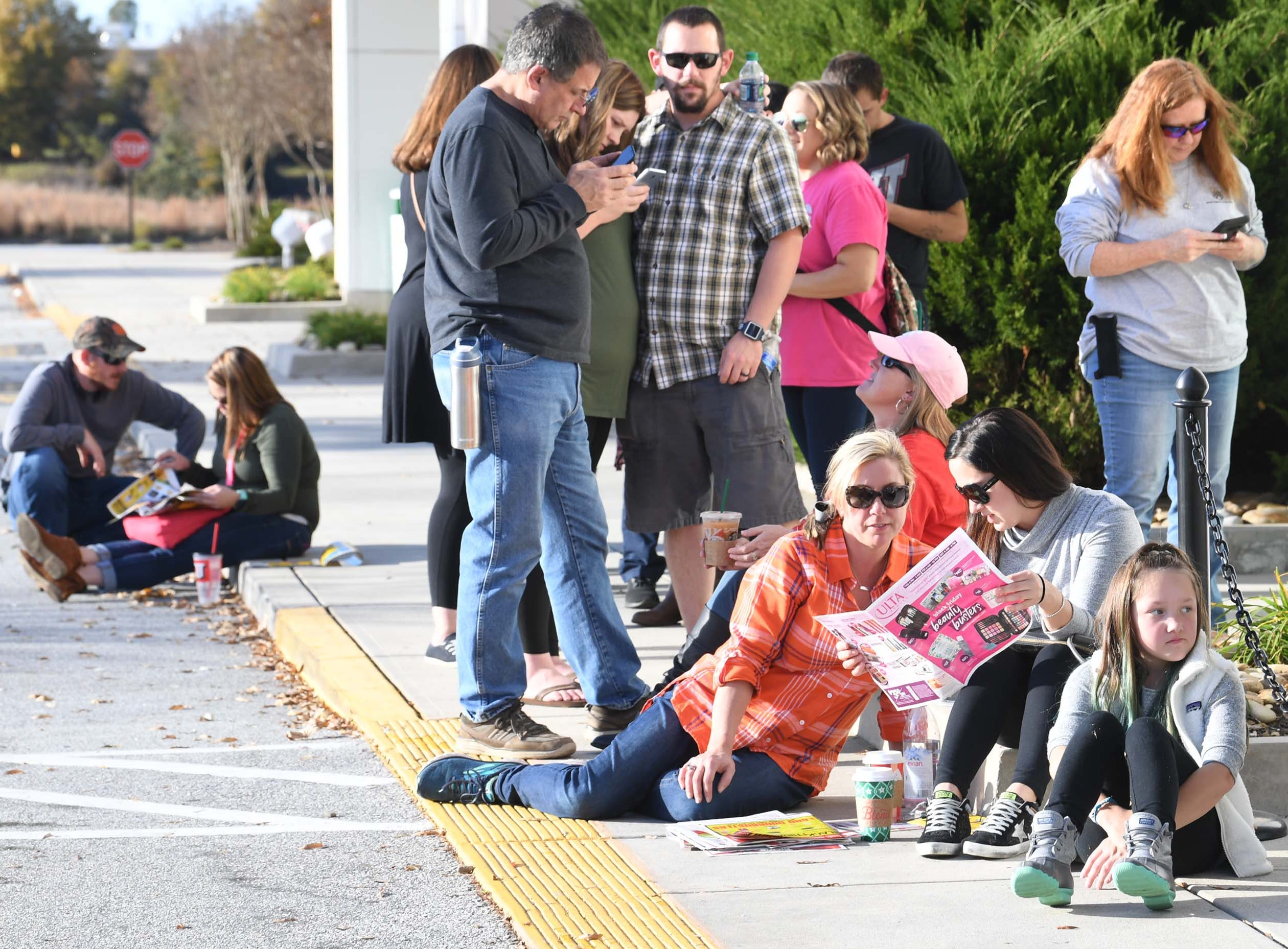 First in line, Sunny Davis, left, Victoria Bonnette, and Lilah Bonnette look at newspaper ads while waiting in line for doors to open for Black Friday sales at Kohl's in Anderson on Thanksgiving Day, Thursday, November 22, 2018.
