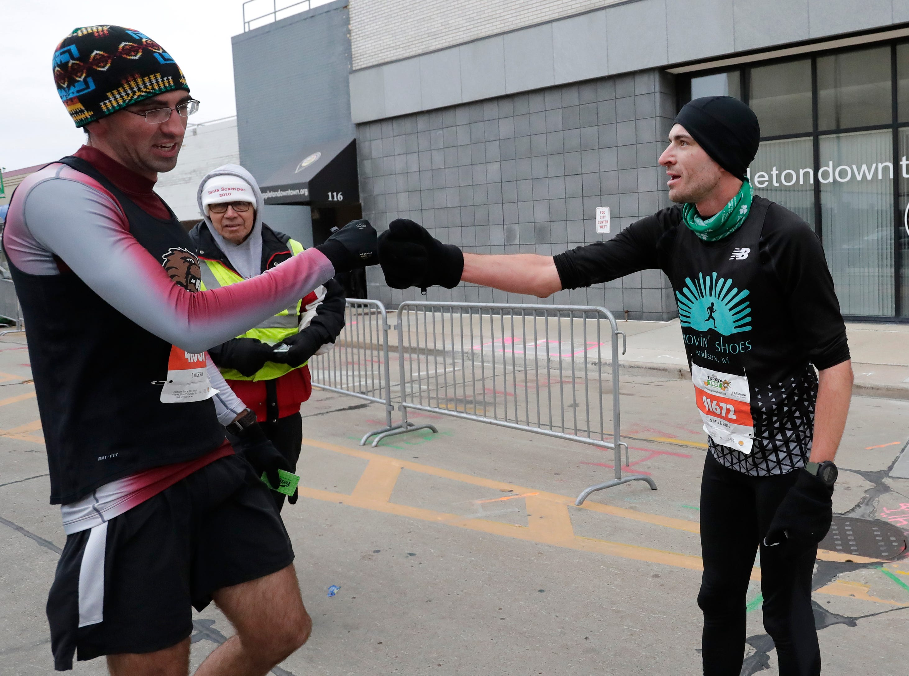 Second place finisher Logan Kitchen, left, of Beaver Dam and first place finisher Alexander Rink of Chilton congratule each other at the finish of the 5-mile run portion of the 11th Annual Festival Foods Turkey Trot Thursday, November 22, 2018, in Appleton, Wis. 