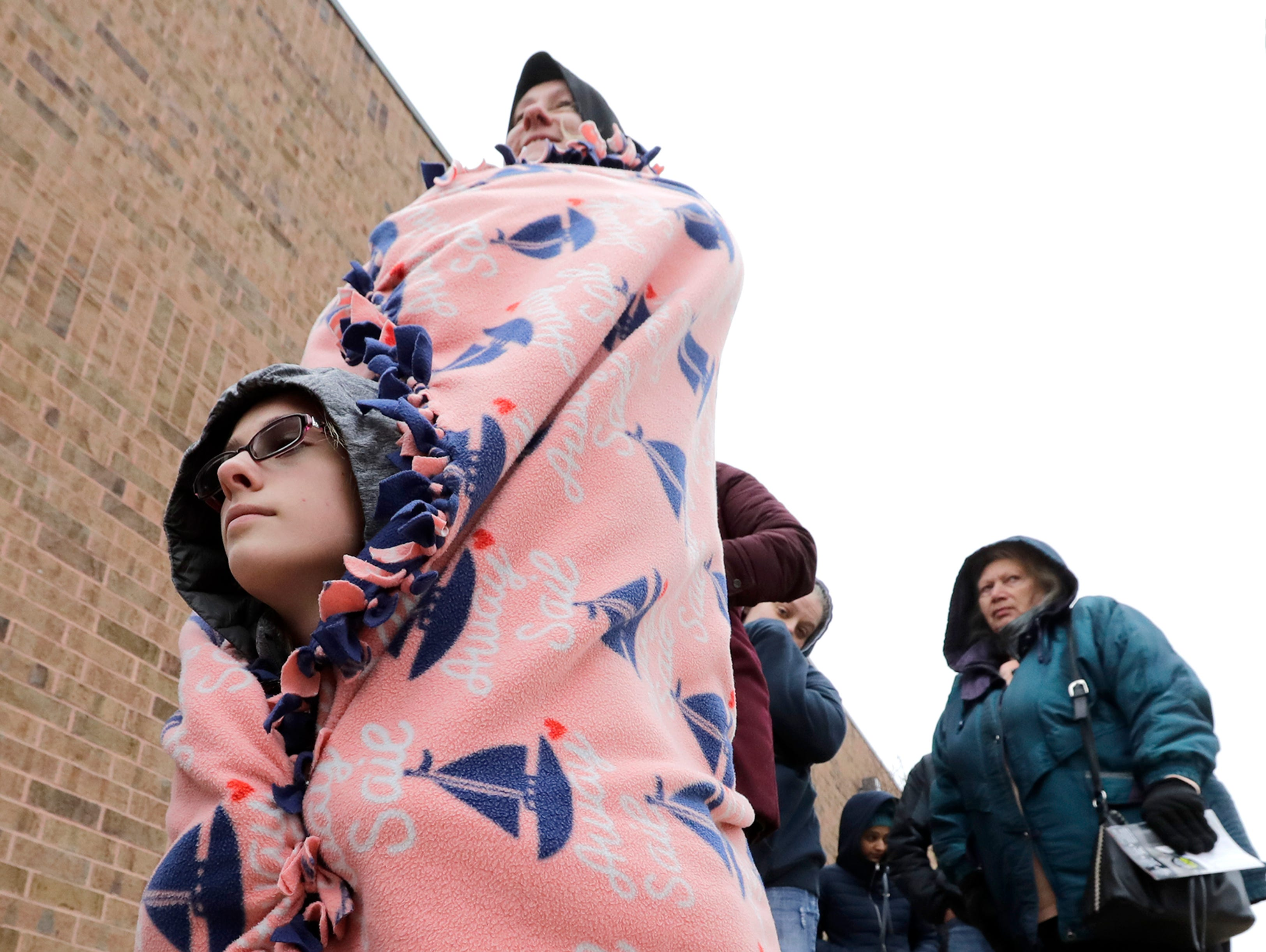 Jennifer Diedrick, bottom, tries to stay warm by crouching under her mother Sadie Diedrick's blanket while waiting in line at JCPenney for Black Friday deals Thursday, November 22, 2018, in Grand Chute, Wis. The two are from Appleton.