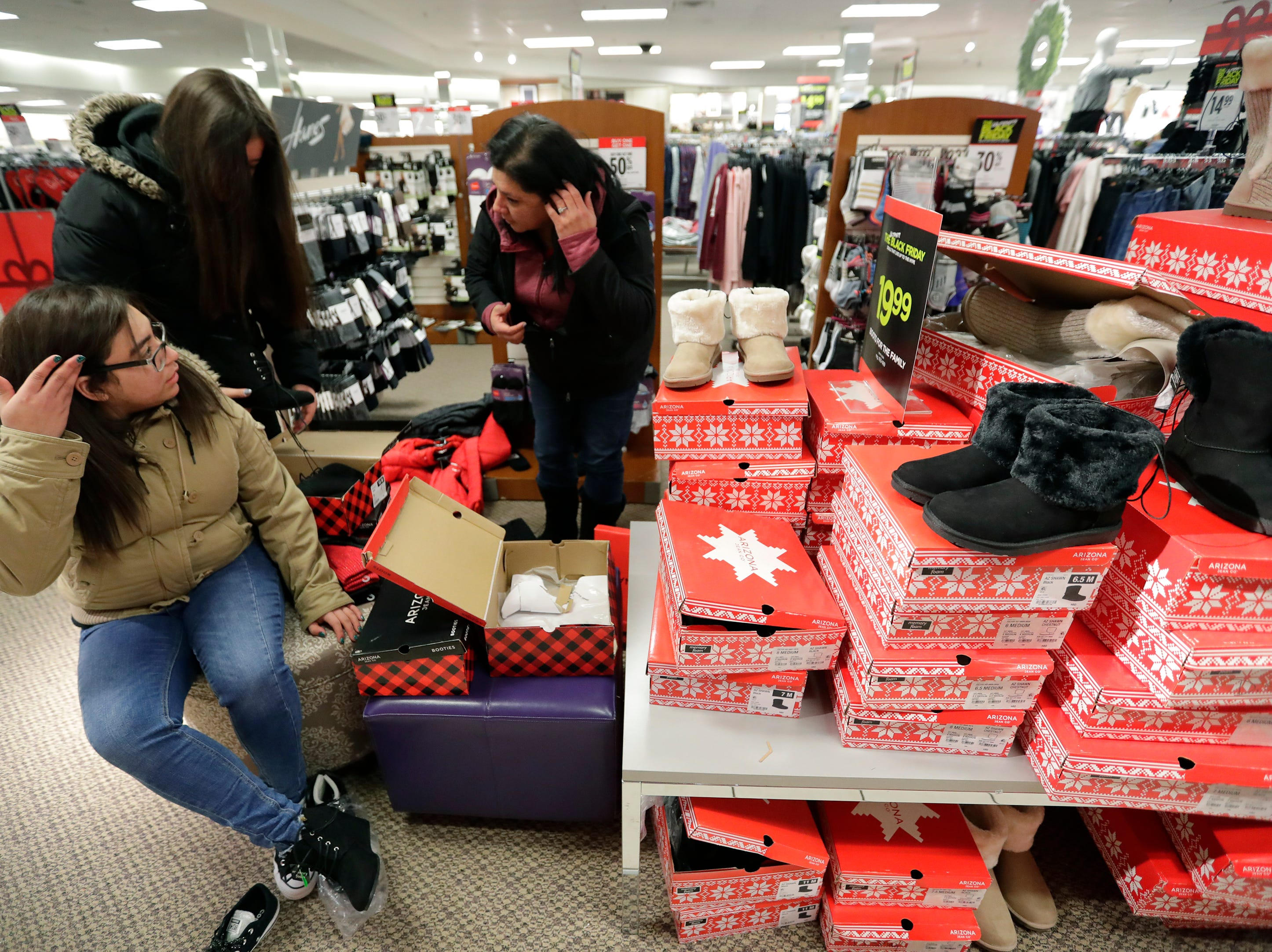 Samantha Polanco, left, 16, Jessica Quintanilla, 14, and their mother Kristy Polanco shop for boots while looking for Black Friday deals at JCPenney Thursday, November 22, 2018, in Grand Chute, Wis. 