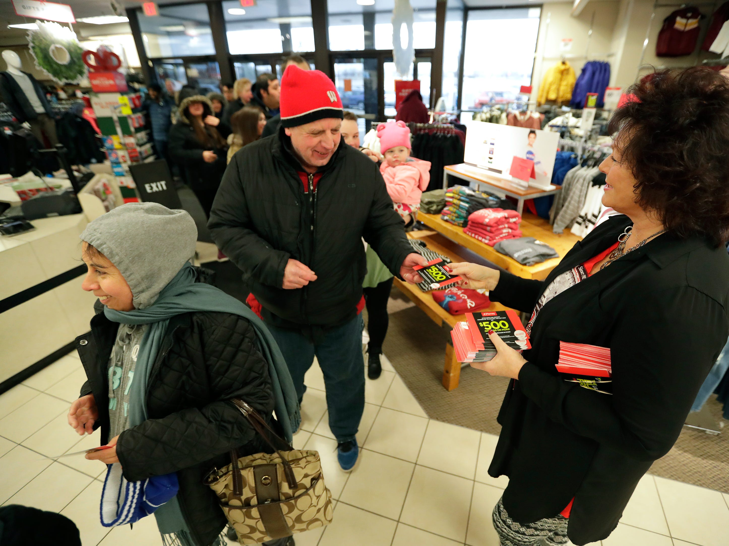 JCPenney employee Deb Kiley, right, hands out special coupons as customers enter the store looking for Black Friday deals Thursday, November 22, 2018, in Grand Chute, Wis. 