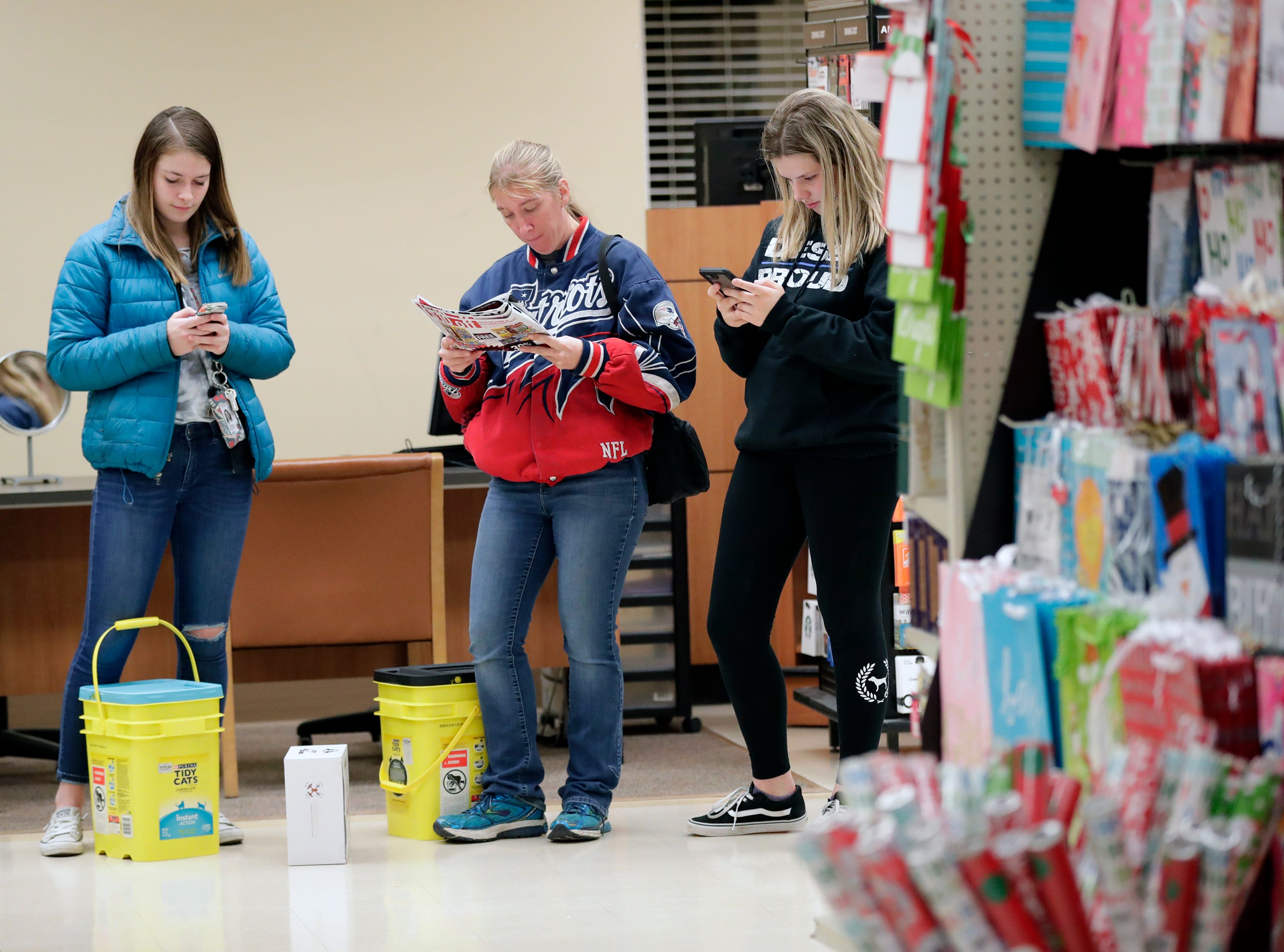 McKinzie Fields, left, Janet Fields and Emily Schertz, right, make a plan of attack for Black Friday specials at Shopko Thursday, November 22, 2018, in Appleton, Wis. The three are from Black Creek.