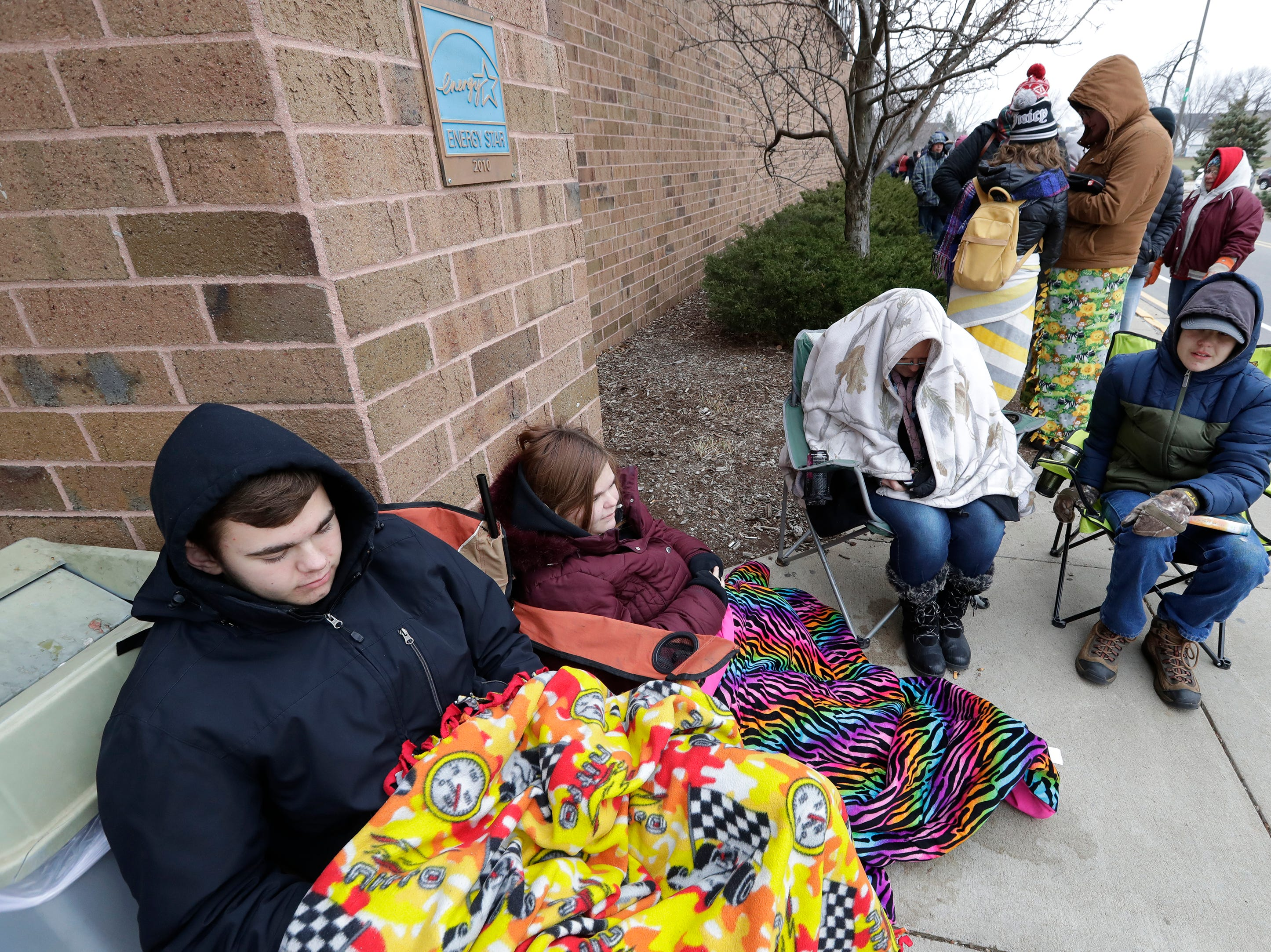 Devon Hajenga, left, Tasha Hajenga, Cindy Kronberg and Dennis Hajenga, right, try to stay warm while waiting in line for JCPenney to open for Black Friday deals Thursday, November 22, 2018, in Grand Chute, Wis. Kronberg is the mother of the three children and all are from Kaukauna.