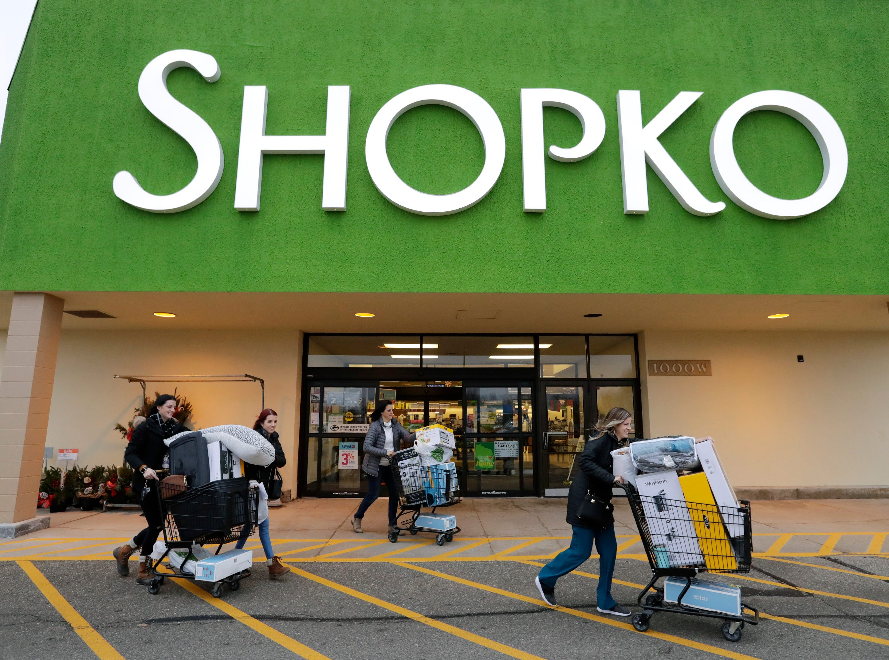 Kayla Williams, left, of Neenah is loaded down with Black Friday specials as she heads to her vehicle with her sister Kendra Miller of Appleton, mother Kelly Miller of Appleton and other sister Kiera Miller, right, of Appleton Thursday, November 22, 2018, at Shopko in Appleton, Wis. 