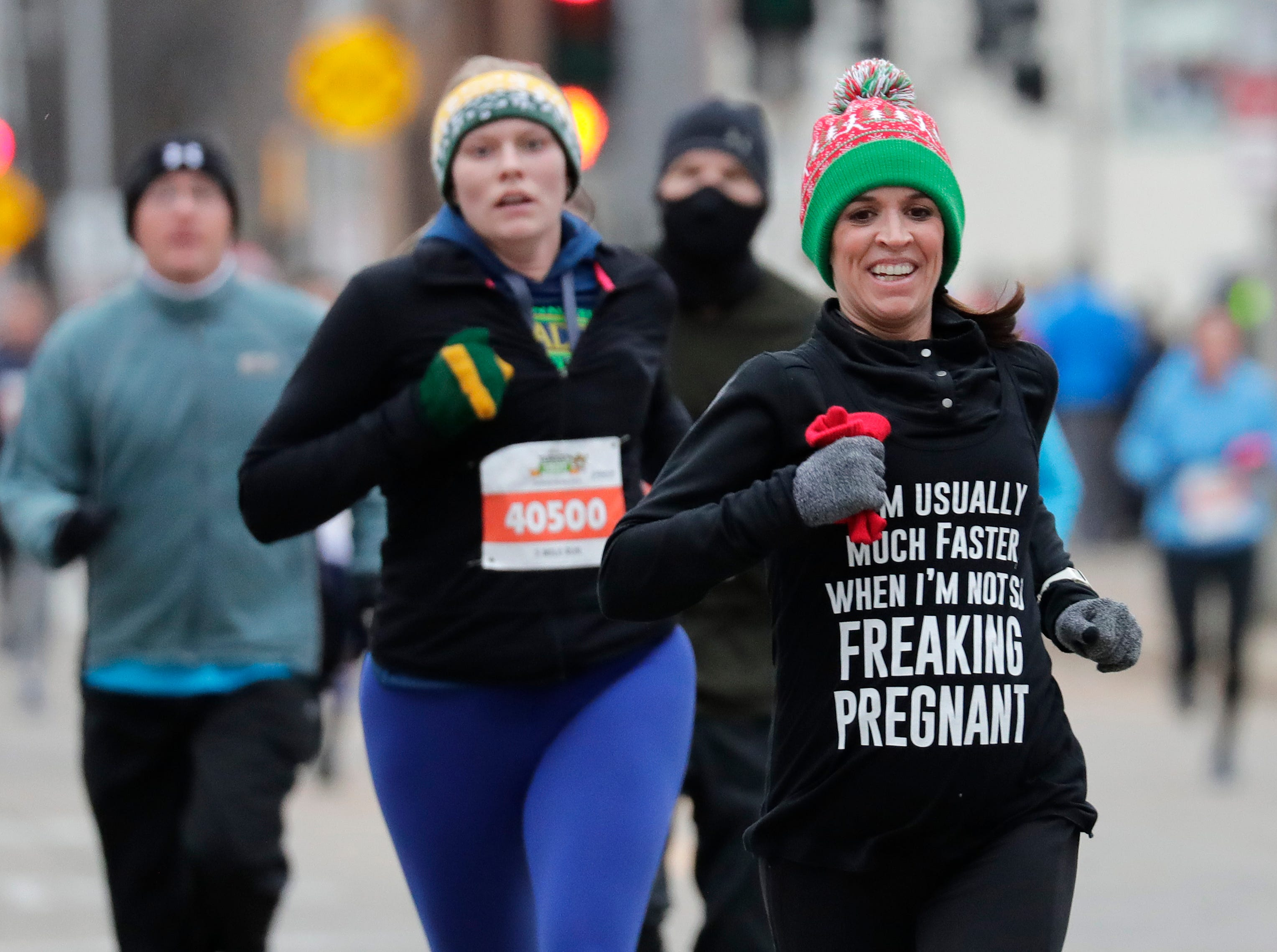Sarah Mahaney, right, of Menasha finishes the 11th Annual Festival Foods Turkey Trot Thursday, November 22, 2018, in Appleton, Wis. 