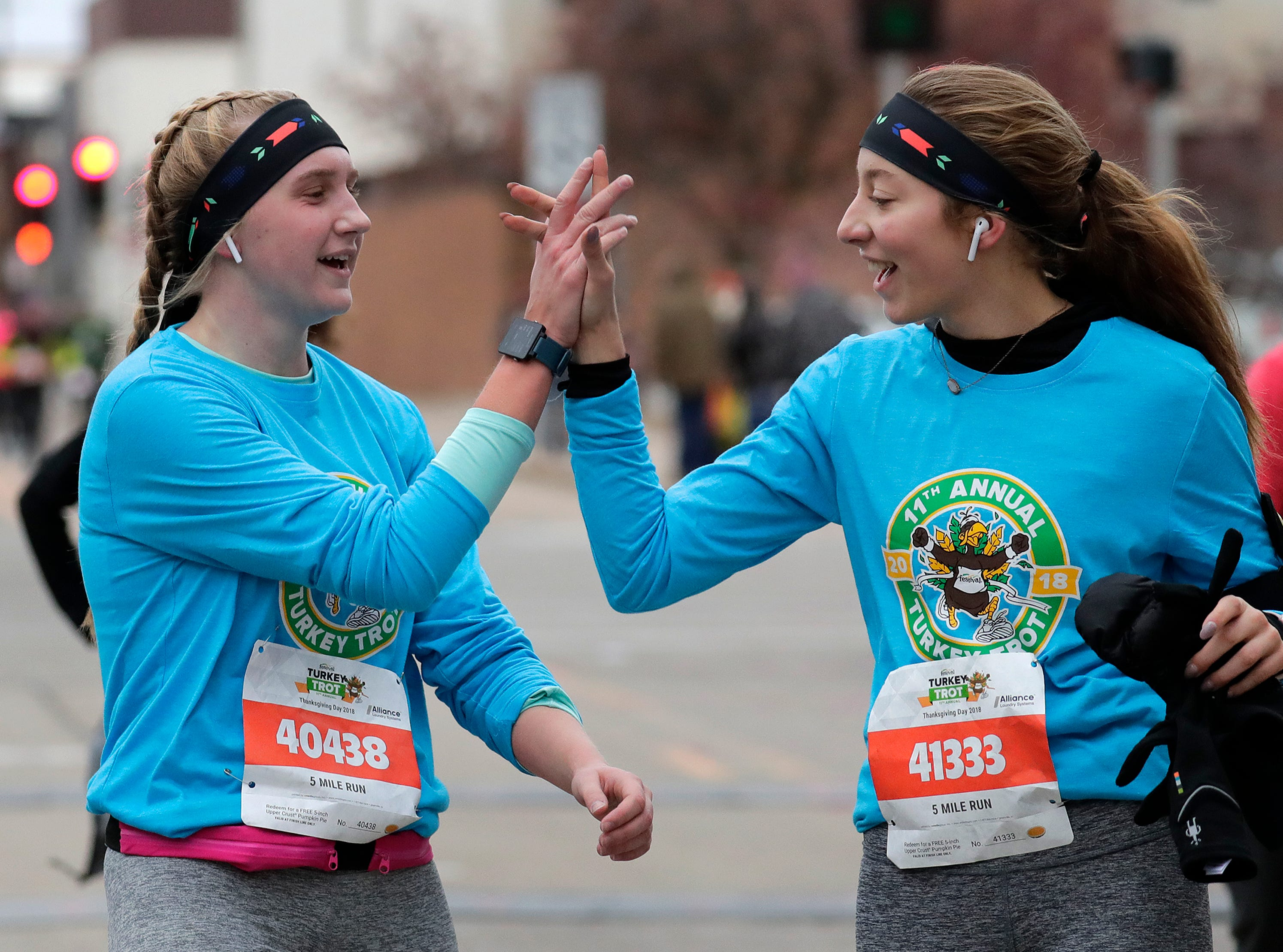 Natalie Dresang, left, and Sarah Messer, both of Kimberly, high-five as they cross the finish line during the 11th Annual Festival Foods Turkey Trot Thursday, November 22, 2018, in Appleton, Wis. 