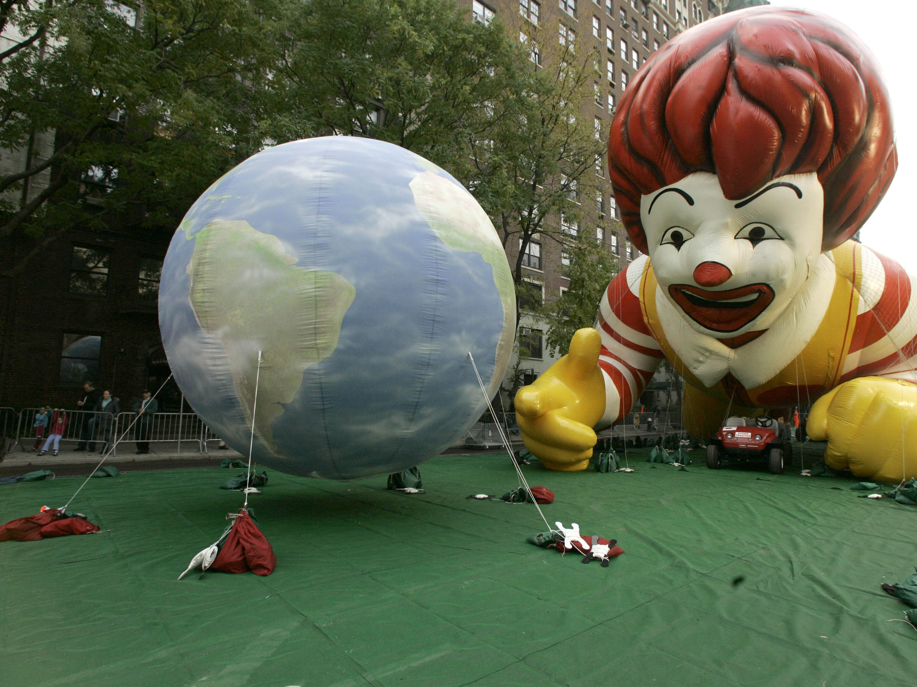 """An earth balloon and the Ronald McDonald balloon are secured to the ground with sand bags during Macy's 81st Annual Thanksgiving Day Parade """"Inflation Eve,"""" Wednesday, Nov. 21, 2007 in New York. Preparations started Wednesday afternoon as giant balloons and many smaller inflatable ones were filled with a helium/air mixture for the Thanksgiving parade march down 5th Ave. (AP Photo/Mary Altaffer)"""