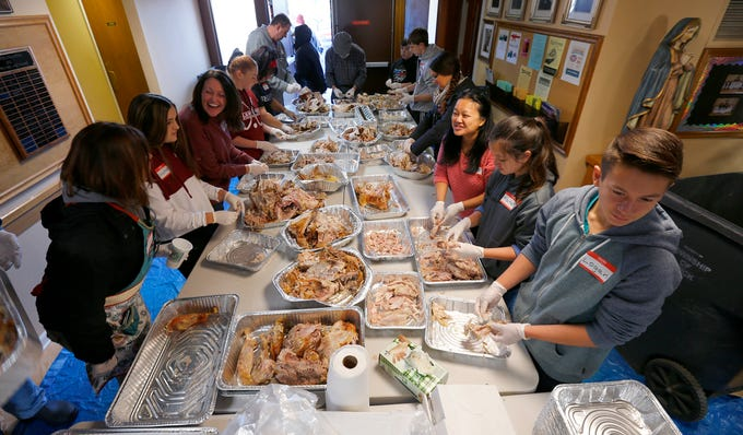 Volunteers pick additional meat off turkeys at The Church of the Epiphany in Brick as they prepare and deliver meals to over 1,200 people in Monmouth and Ocean counties on Thanksgiving Day, November 22, 2018.