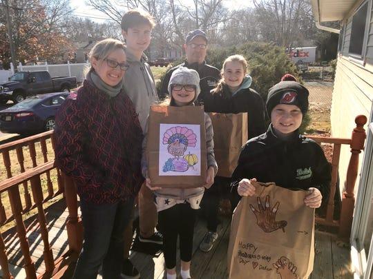 The Ebinger family poses before they deliver a Thanksgiving meal to a home in Brick from from the Church of the Epiphany. From left to right: Theresa Ebinger, 45, Daniel Ebinger, 17, Megan Ebinger, 12, Todd Ebinger, 44, Sarah Ebinger, 15, James Ebinger, 9.