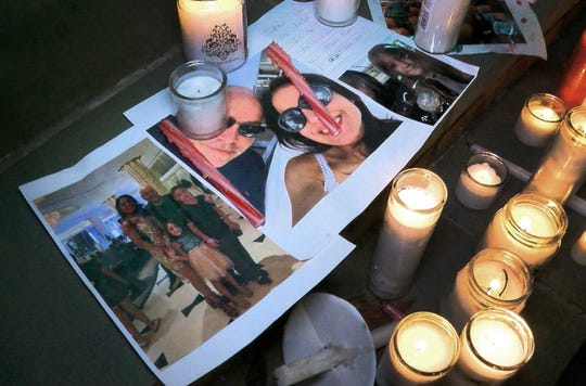 Photos of Keith Caneiro, his wife Jennifer, and children Jesse and Sophia are shown under candles during a vigil held outside the Colts Neck Town Hall Wednesday night, November 21, 2018.  The family was killed in a house fire the previous day.