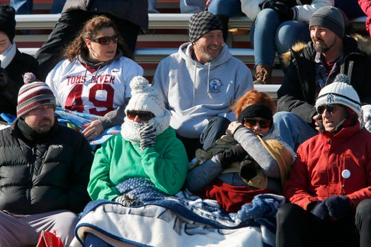 People brace against the cold during the Lakewood at Toms River South football game at Detwiler Stadium, in Toms River, Thursday, November 22, 2018.