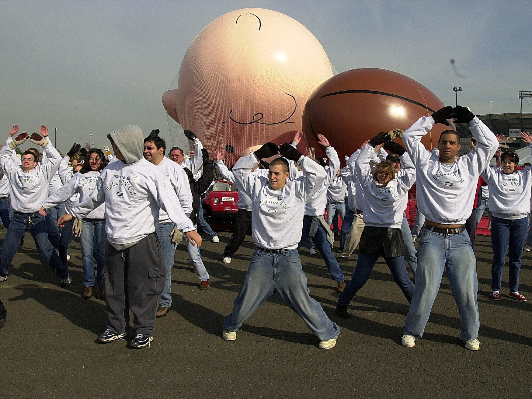 """-  -Balloon handlers warm up before taking the new """"Charlie Brown """" balloon for a test flight at The Meadowlands Sports Complex in East Rutherford, NJ on Saturday, November 9, 2002. The balloonfest is held every year to give a trial run to new balloons before the Macy's Thanksgiving Day parade.(Rohanna Mertens for The Journal News11/09/02)"""