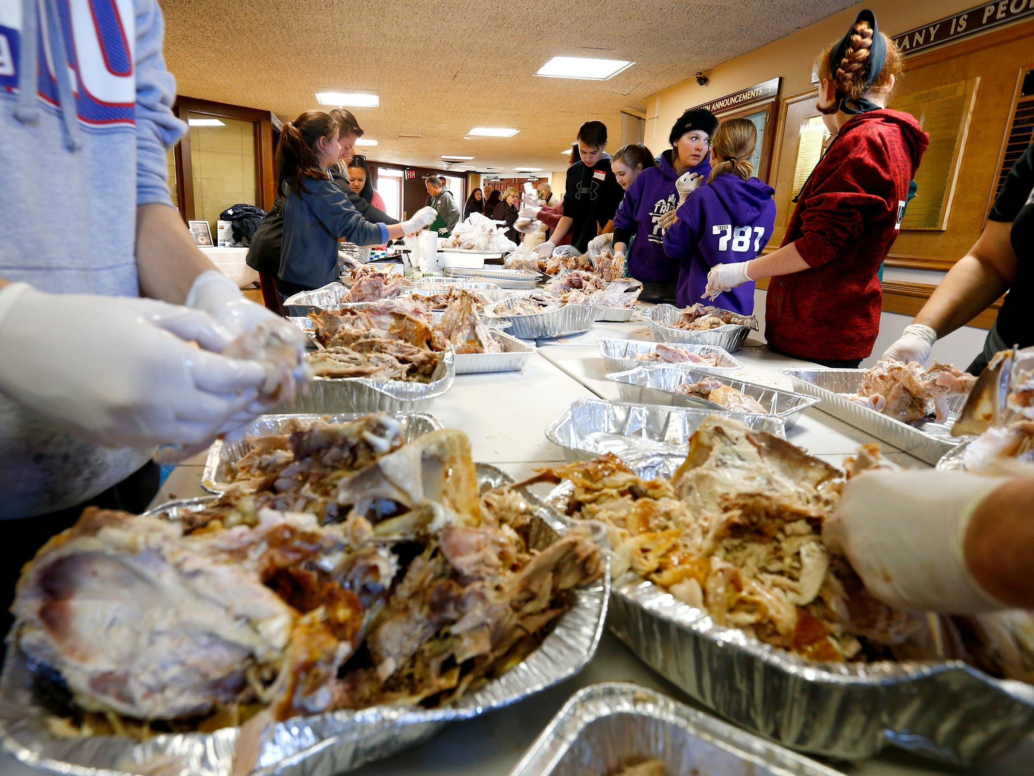 Volunteers clean additional meat off turkeys at The Church of the Epiphany in Brick as they prepare and deliver meals to over 1,200 people in Monmouth and Ocean counties on Thanksgiving Day, November 22, 2018.