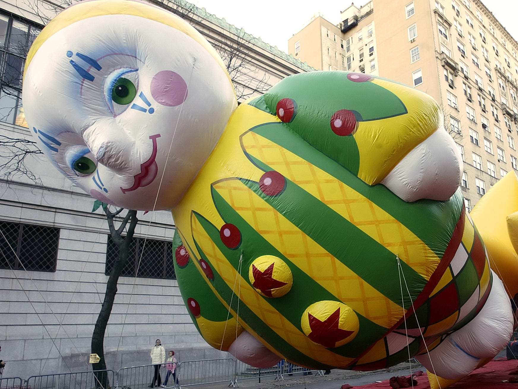 A balloon sits tethered to weights as people pass the day before the Macy's Parade in New York Wednesday, Nov. 23, 2005. Balloon workers were busy Wednesday, as the readied the balloons for tomorrow's 79th Macy's Parade, which will feature 14 giant balloons, 37 smaller ones and 27 floats.   (AP Photo/Gregory Bull)