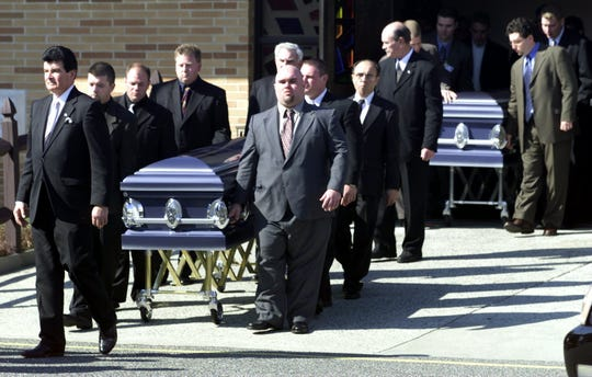 Suzanne LaVecchia and Thomas Luyster's cakets are wheeled from St. Justin's Church in Toms River after their 2002 funeral mass. The two were killed in the Tyler Drive shooting spree by John W. Mabie.