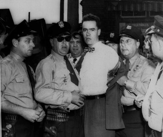 In this Sept. 6, 1949 picture, Howard Unruh, center, is shown with police after his capture in Camden. Unruh committed a mass murder the day before, gunning down 13 people, in an era when such killings were still rare. He died in 2009 in a Trenton nursing facility after an extended illness. (AP Photo)