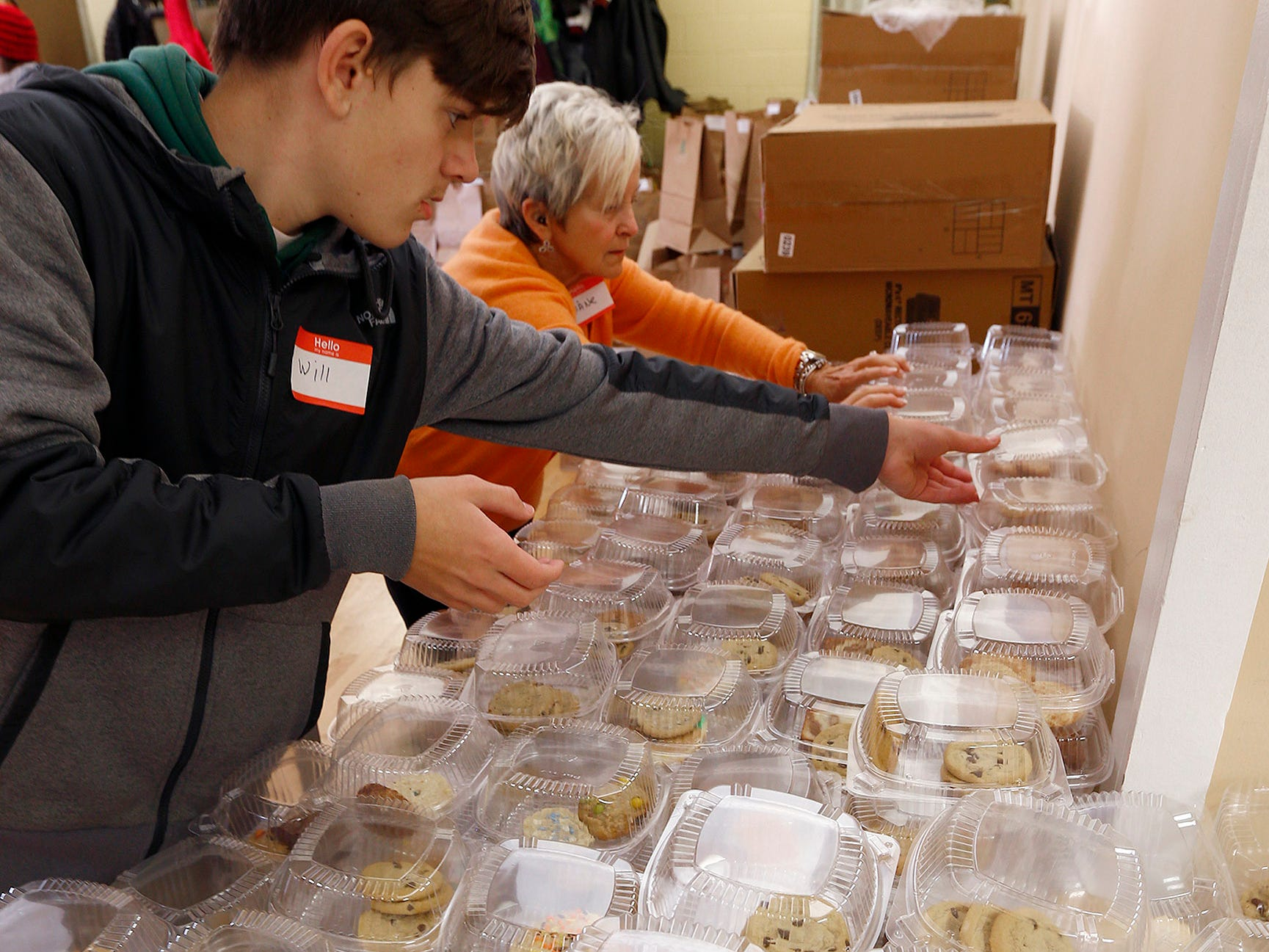 Will Crate, 13,, helps Diane Ponsiglione, both Brick, stack cookies at The Church of the Epiphany in Brick as they prepare and deliver meals to over 1,200 people in Monmouth and Ocean counties on Thanksgiving Day, November 22, 2018.