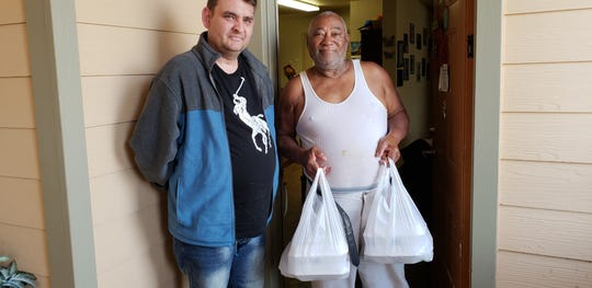 Volunteer and U.S. Marine Corps veteran Ron Howard (left) delivered Thanksgiving lunches to Army veteran Willie Williams and his family Thursday as part of Operation Thanksgiving, a yearly effort of the Taylor County Veterans Services Office.
