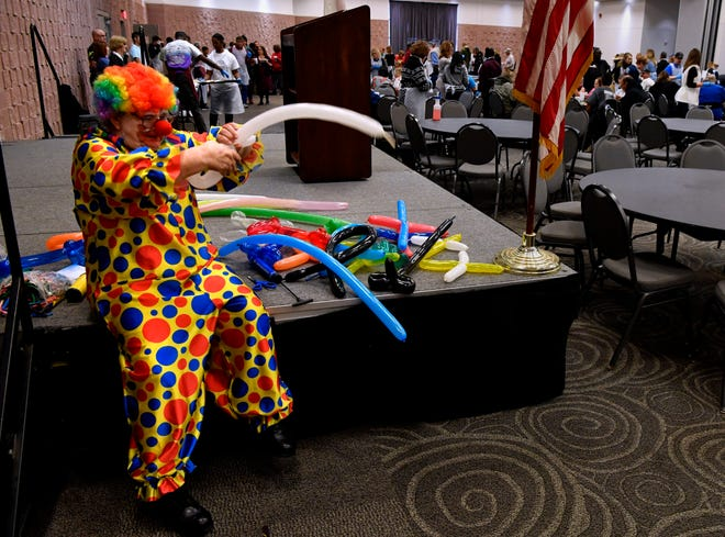 """Gloria Hickman as Happy the Clown makes a balloon animal during Operation Thanksgiving at the Abilene Convention Center. She said she had enough balloons to make 388 figures. """"The kids always ask for one and sometimes the adults do, too,"""" she said. The annual free holiday meal is sponsored by the Taylor County Veterans Service Office."""
