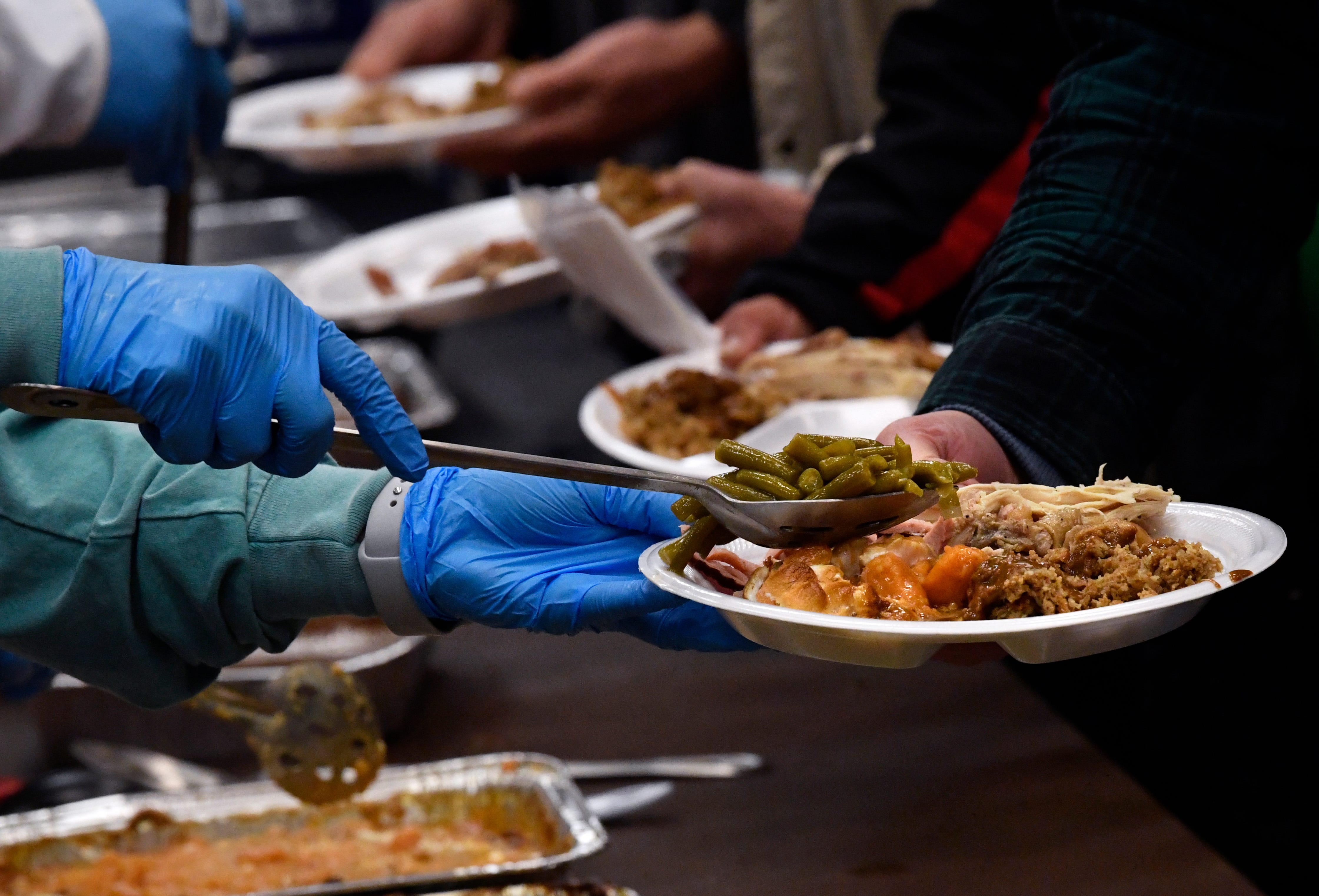 Volunteers serve green beans, turkey, ham, stuffing and sweet potatoes during Operation Thanksgiving Thursday.