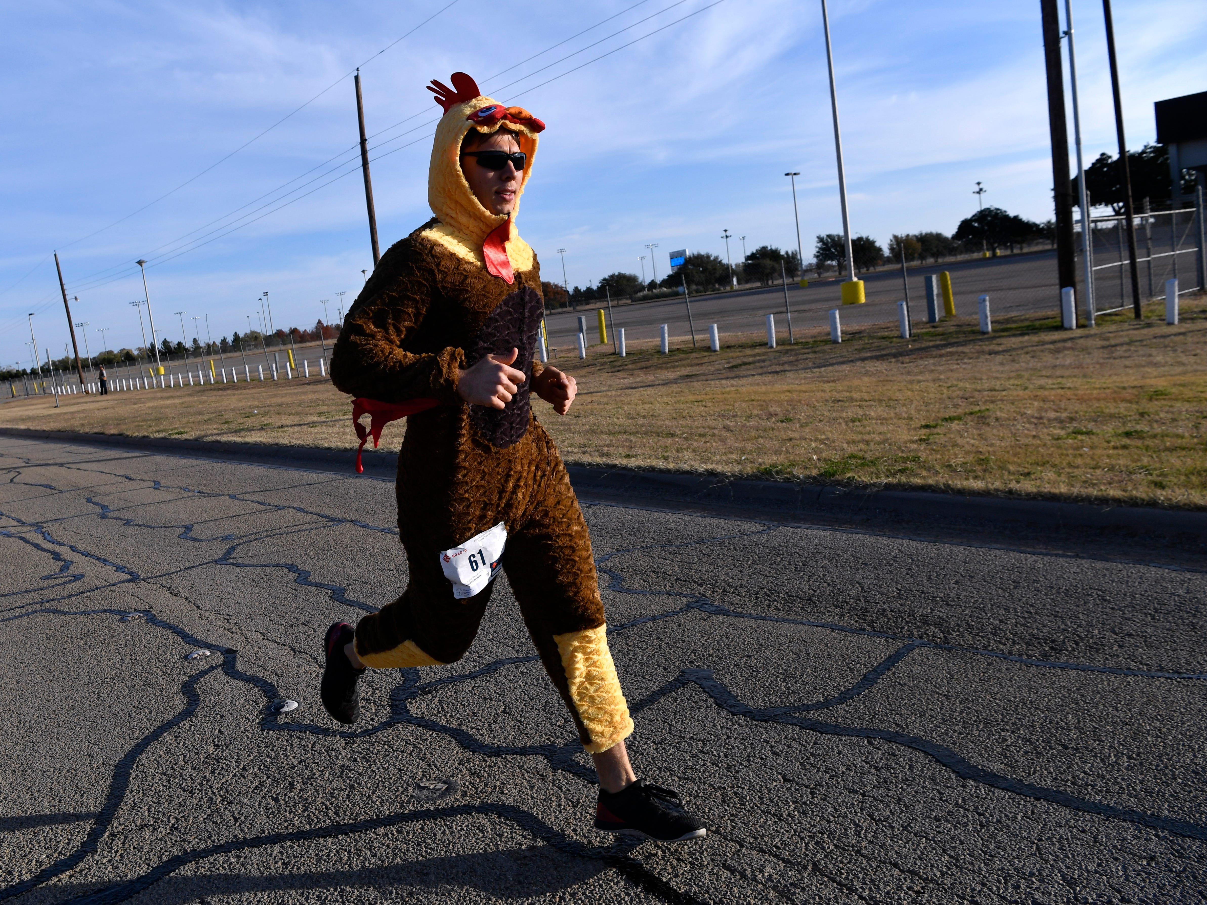 "Josh Boynton sidesteps the crowd at the beginning of the Abilene Turkey Trot 5K wearing a turkey suit. He and friend Rob Jacques both wore the outfits and while festive for the Thanksgiving holiday, realized soon during the run that the garments didn't breath very well. ""We were basting in our natural juices,"" Boynton joked. Sponsored by the Abilene Runners Club, the Thanksgiving 5K course started at Shotwell Stadium, went through the adjacent Lytle neighborhood, then finished back at Shotwell. Proceeds benefited the West Texas Rehab Center and the Abilene Runners Club; their motto for the day was, ""Walk/run 3.1 miles and eat guilt free the rest of the day!"""