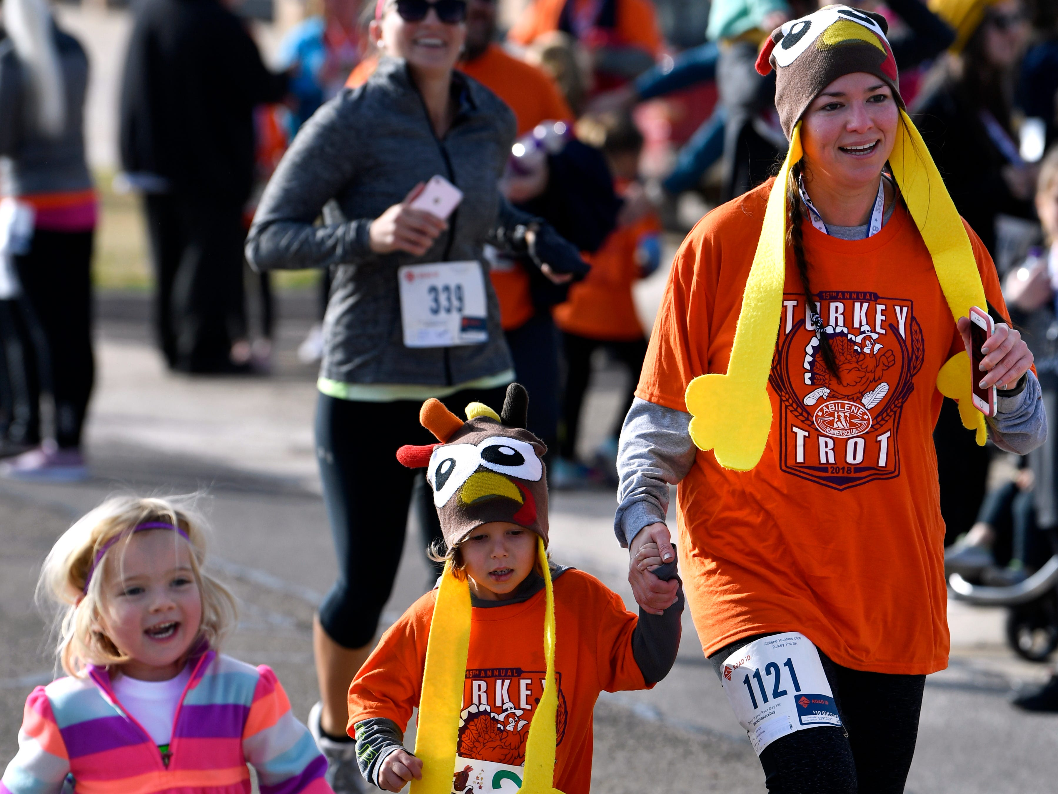 "Maizey Hughes, 3, joins Shandy Sarchet, and her 4-year-old son Corbyn as they finish the one-mile fun-run during the Abilene Turkey Trot Thursday Nov. 22, 2018. The course took the kids twice around Shotwell Stadium. Sponsored by the Abilene Runners Club, the larger Thanksgiving 5K course started at Shotwell, went through the adjacent Lytle neighborhood, then finished back at the stadium. Proceeds benefited the West Texas Rehab Center and the Abilene Runners Club; their motto for the day was, ""Walk/run 3.1 miles and eat guilt free the rest of the day!"""