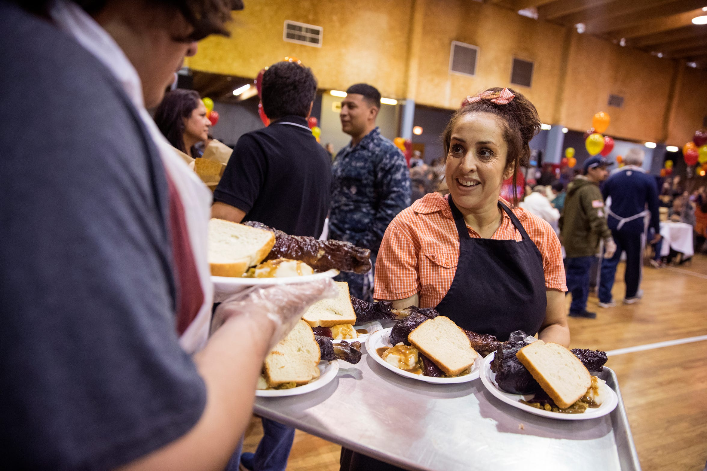 Volunteers Brayden Burrows (left) and Lynn Villarreal deliver meals during the 75th annual Joe Salem Dinner at Sokol Gym on Thanksgiving on Thursday, November 22, 2018.