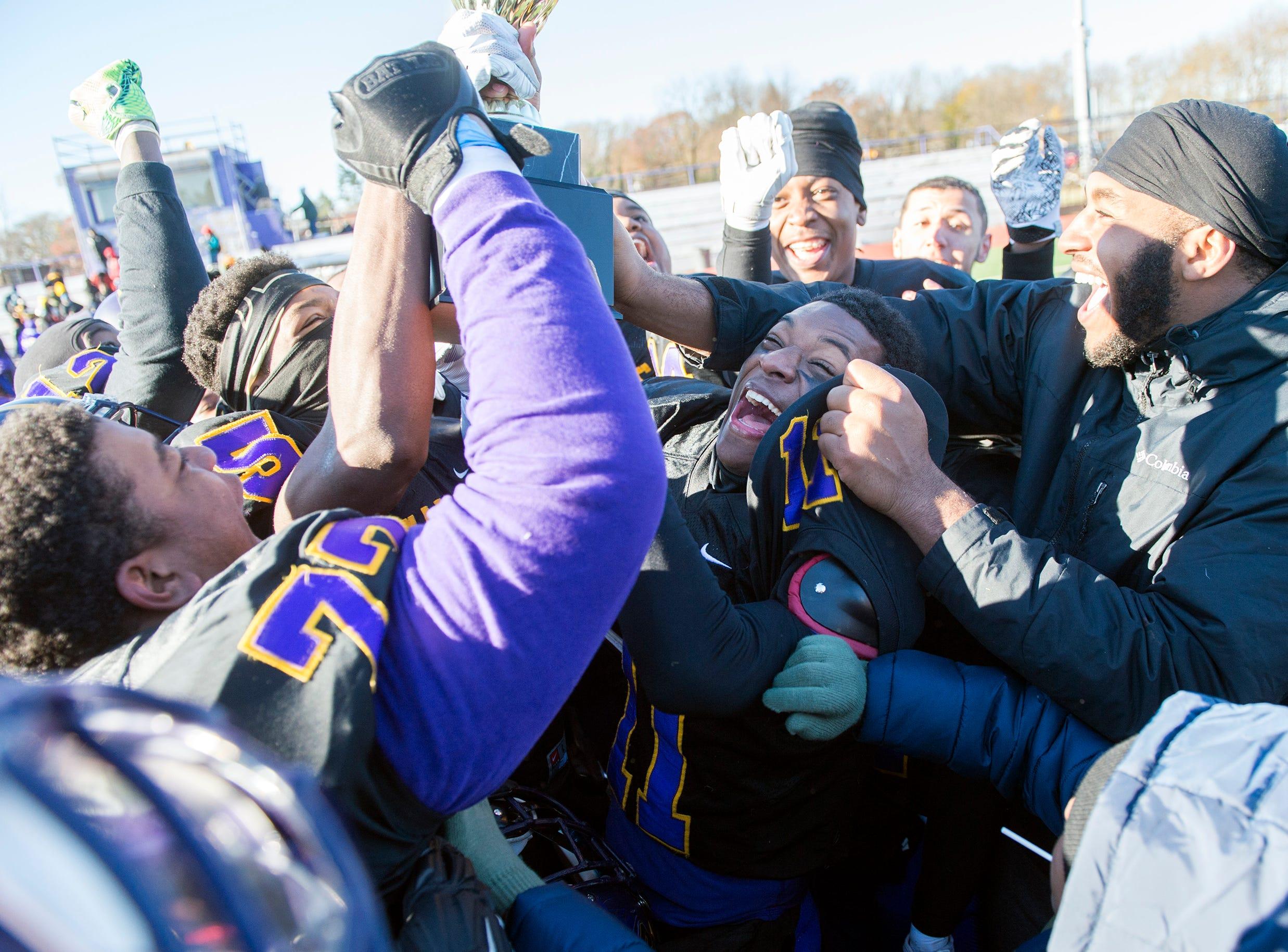 Camden teammates celebrate following an annual Camden-Woodrow Wilson Thanksgiving game Thursday, Nov. 22, 2018 in Camden, N.J. Camden won 39-28.