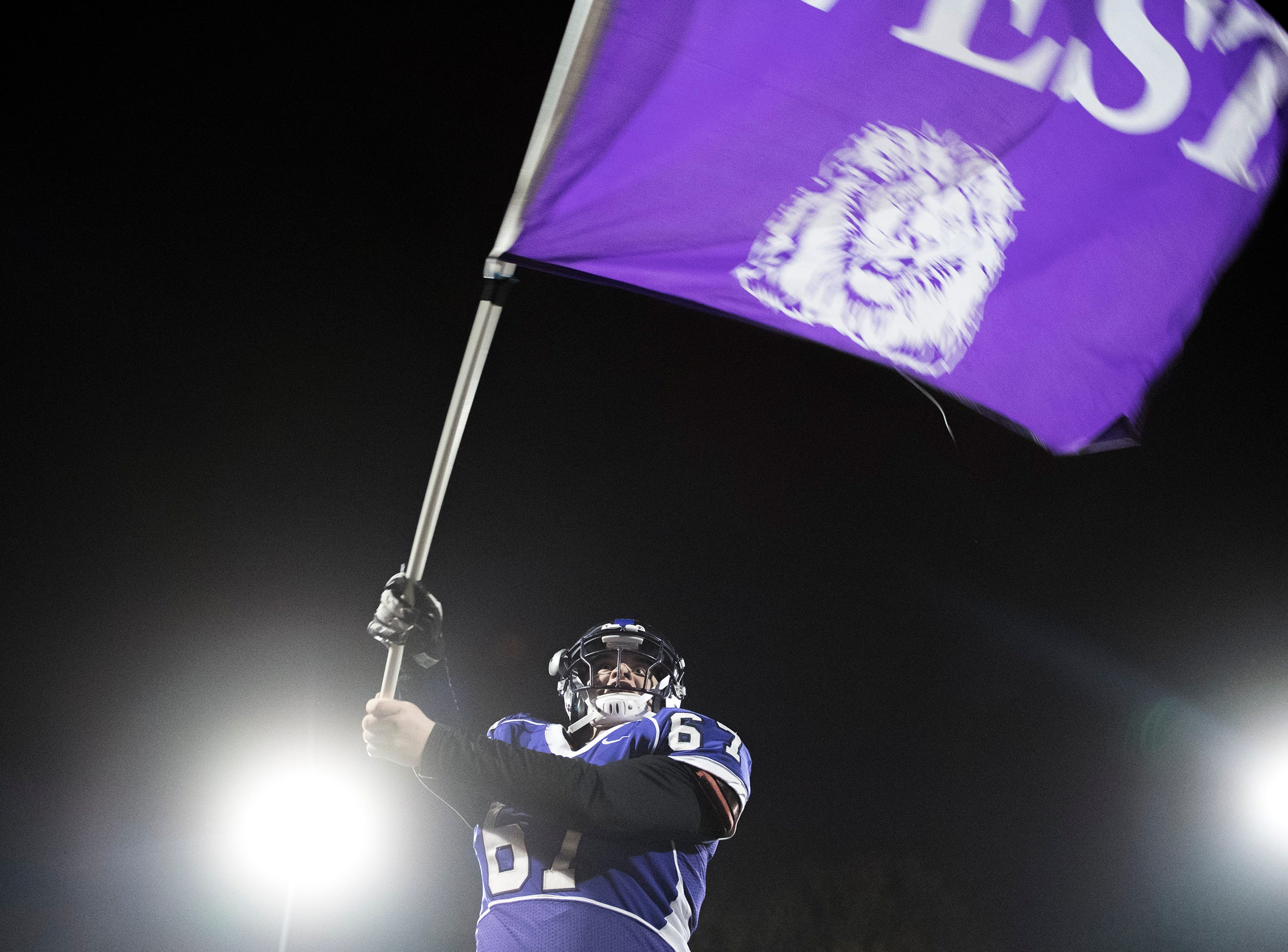 West's Seamus Curran (67) waves the school flag before winning an annual East-West game Wednesday, Nov. 21, 2018 at Cherry Hill West High School in Cherry Hill, N.J. West won 22-7.
