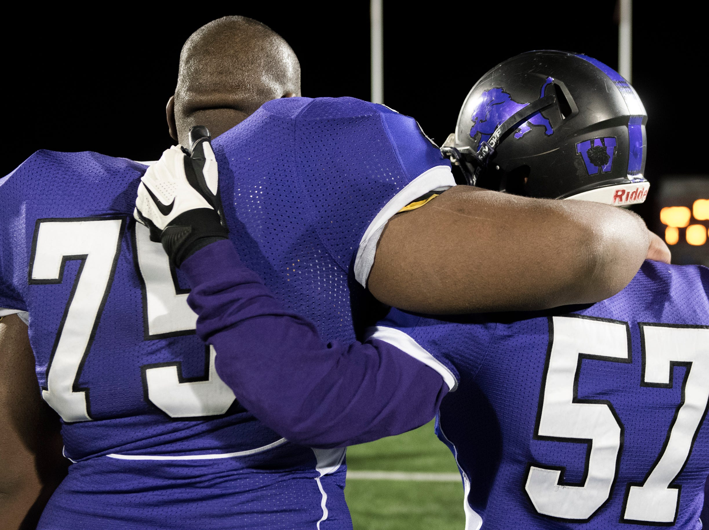 West's Kevin Schindler (75) and Lenin Leon Fernandez (57) embrace following an annual East-West game Wednesday, Nov. 21, 2018 at Cherry Hill West High School in Cherry Hill, N.J. West won 22-7.