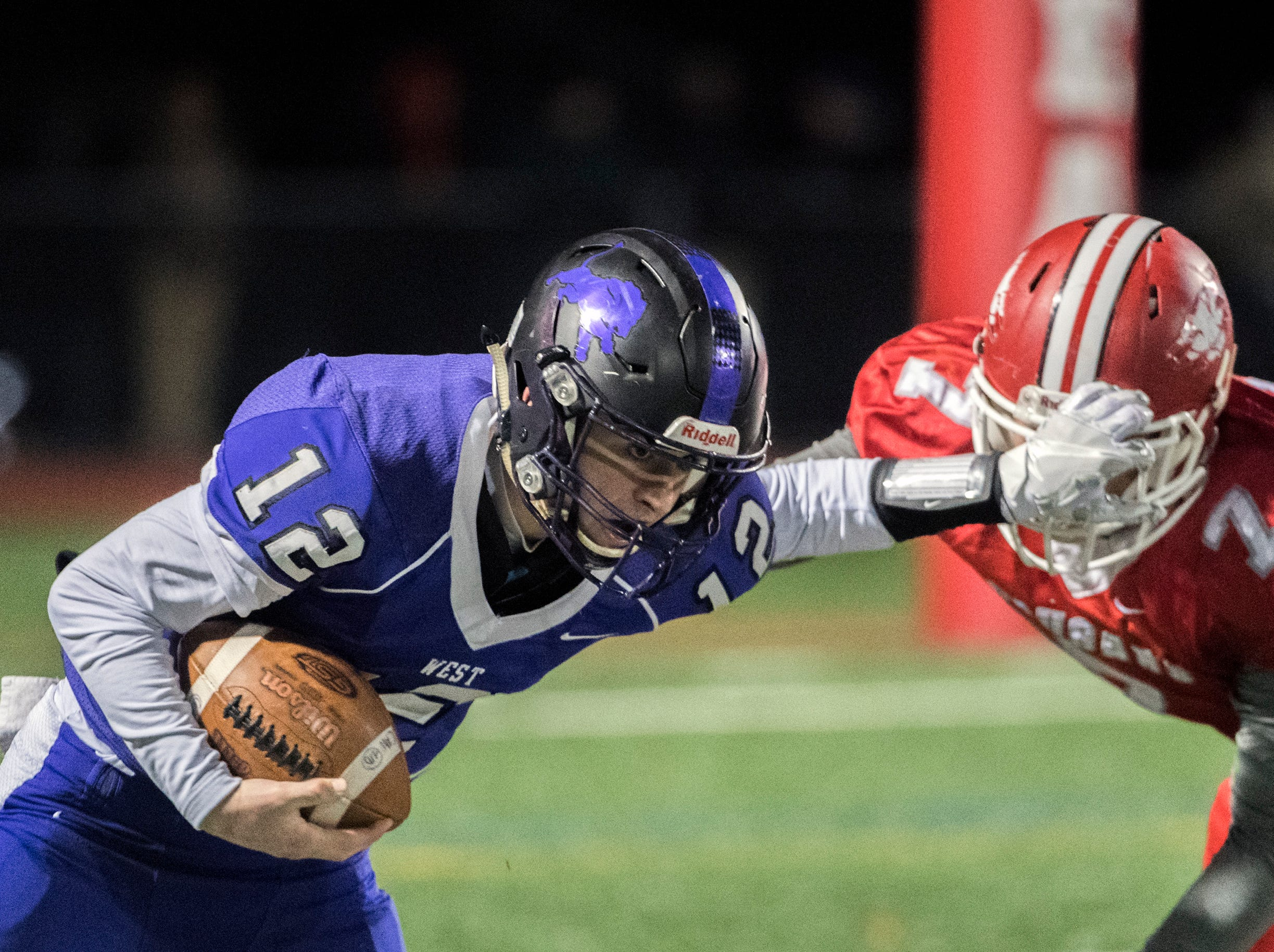 West quarterback Nick Arcaroli (12) stiff-arms East's Nick Gazzola (7) Wednesday, Nov. 21, 2018 at Cherry Hill West High School in Cherry Hill, N.J.