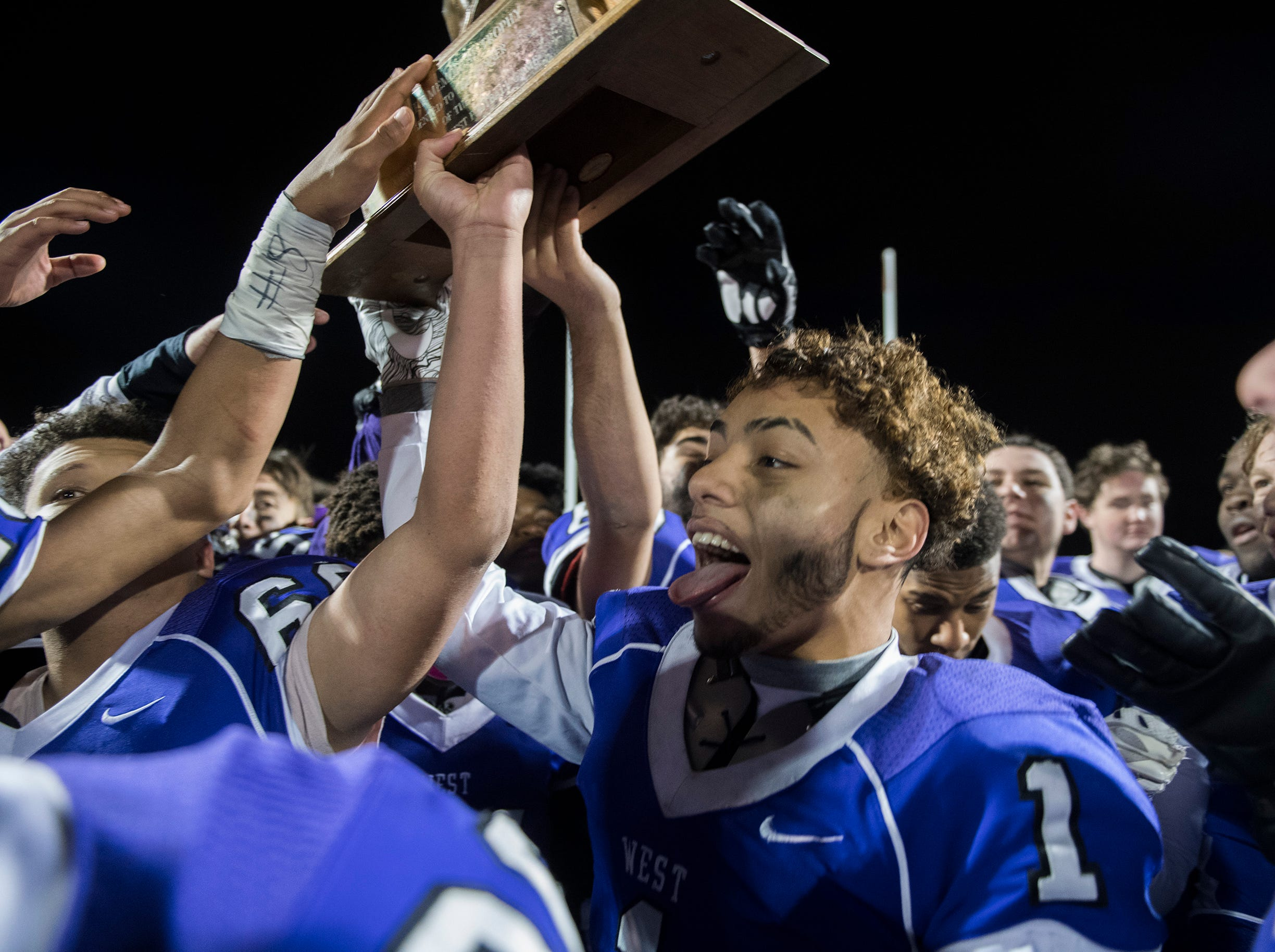 West's Carlos Gomez Jr. (1) raises the Al DiBart trophy following a win in the annual East-West game Wednesday, Nov. 21, 2018 at Cherry Hill West High School in Cherry Hill, N.J. West won 22-7.