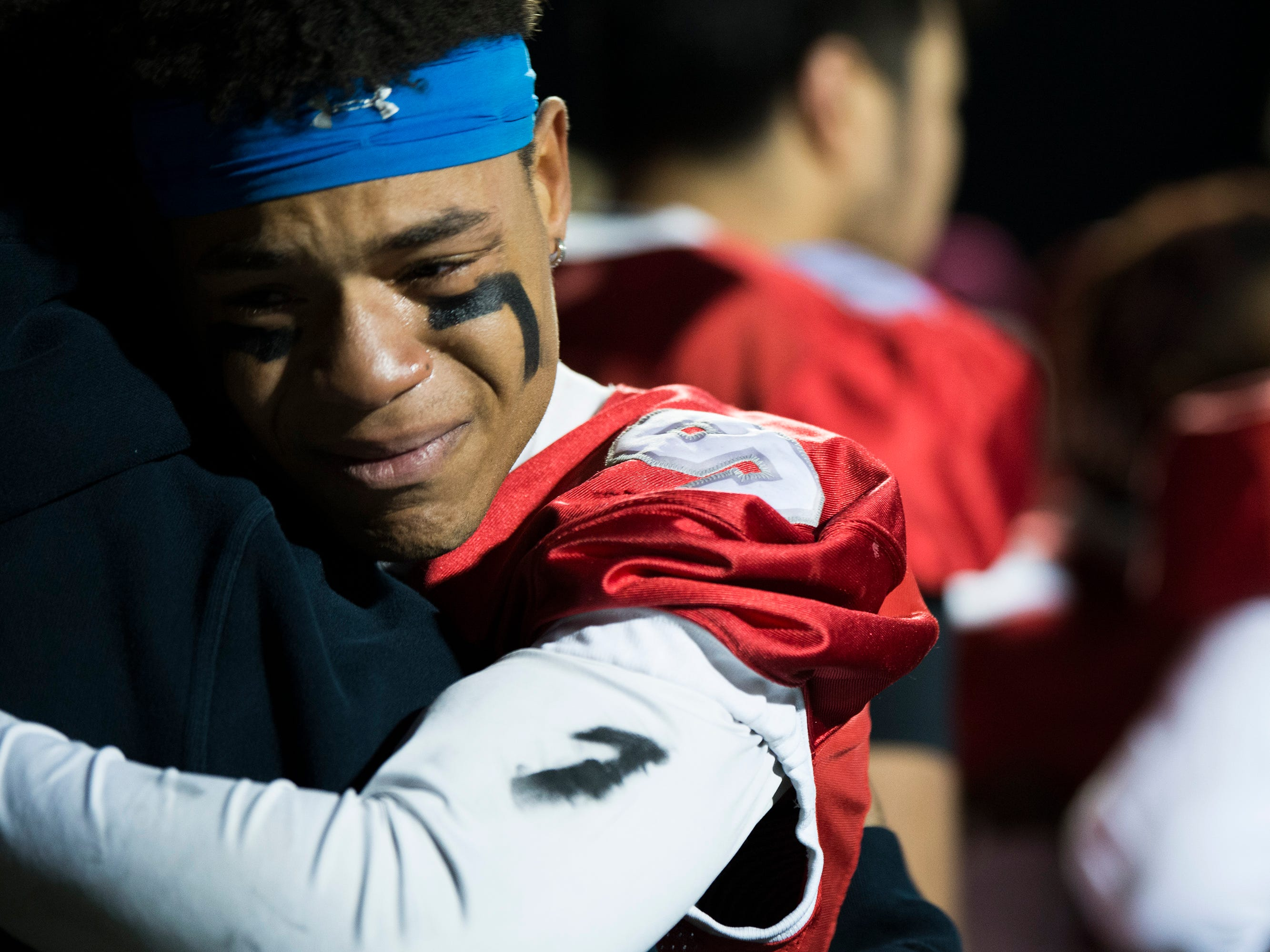 East's Elijah Adkins (9) is embraced following a loss in the annual East-West game Wednesday, Nov. 21, 2018 at Cherry Hill West High School in Cherry Hill, N.J. West won 22-7.