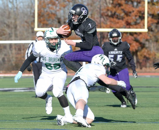 Old Bridge quarterback Owen Haughney leaps over East Brunswick defenders on Thursday, Nov. 22, 2018.