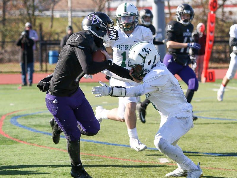 Old Bridge quarterback Owen Haughney (left) tries to hold off East Brunswick's Derrick Davis on Thursday, Nov. 22, 2018.