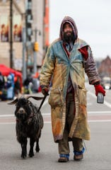 Erick Brown and his goat Deer walk down Woodward Avenue before the 92nd America's Thanksgiving Day Parade in Detroit, Thursday, Nov. 22, 2018.