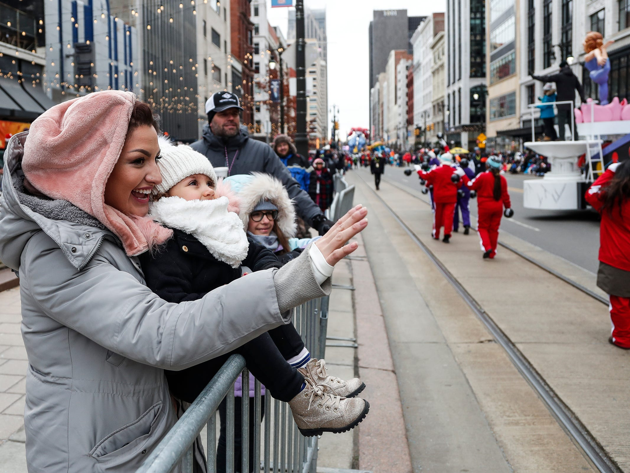 Lauren Martorana and her daughter Elly Martorana, 2, both of Farmington wave at the parade participants during the 92nd America's Thanksgiving Day Parade in Detroit, Thursday, Nov. 22, 2018.