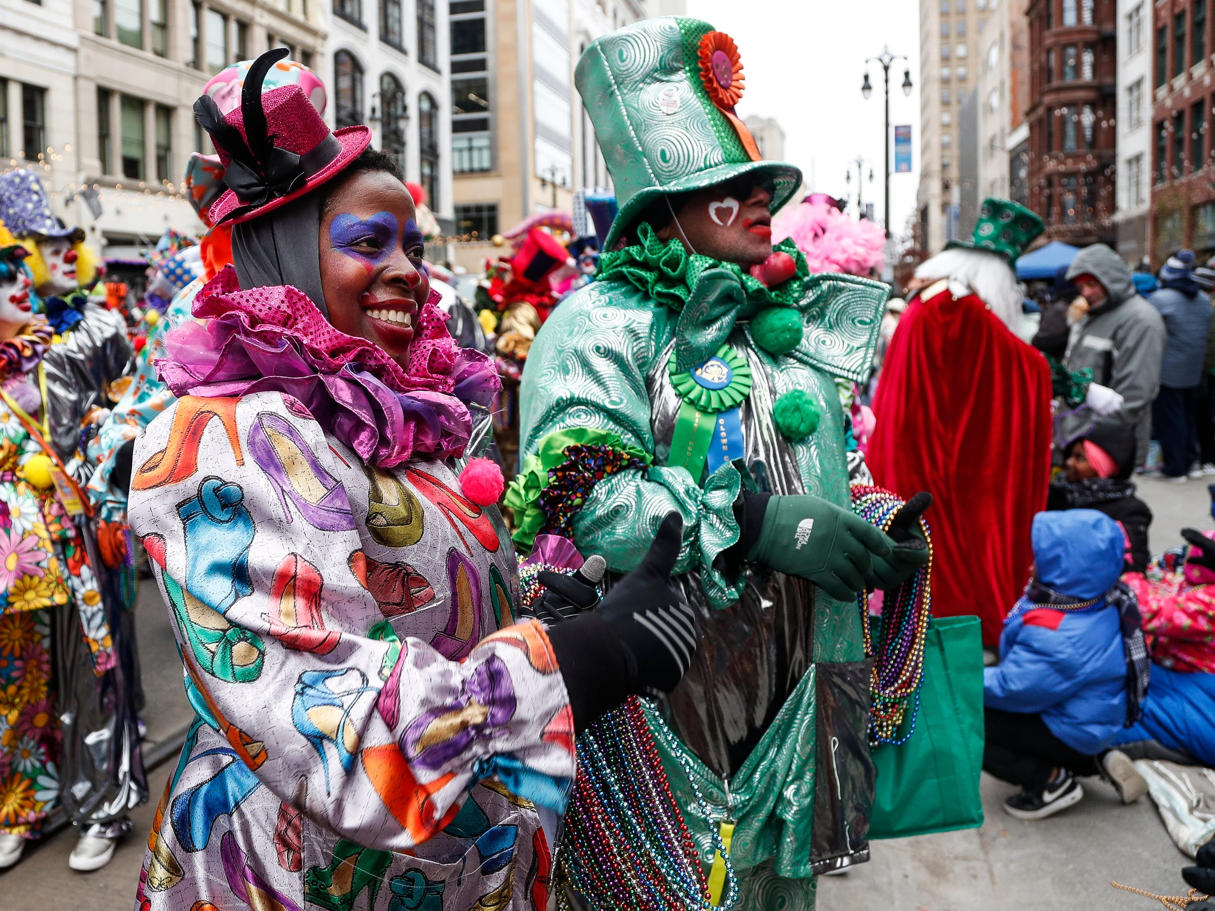 Saunteel Jenkins and her husband Carl Bentley, both members of the Distinguished Clown Corps hand out beads to spectators during the 92nd America's Thanksgiving Day Parade in Detroit, Thursday, Nov. 22, 2018.