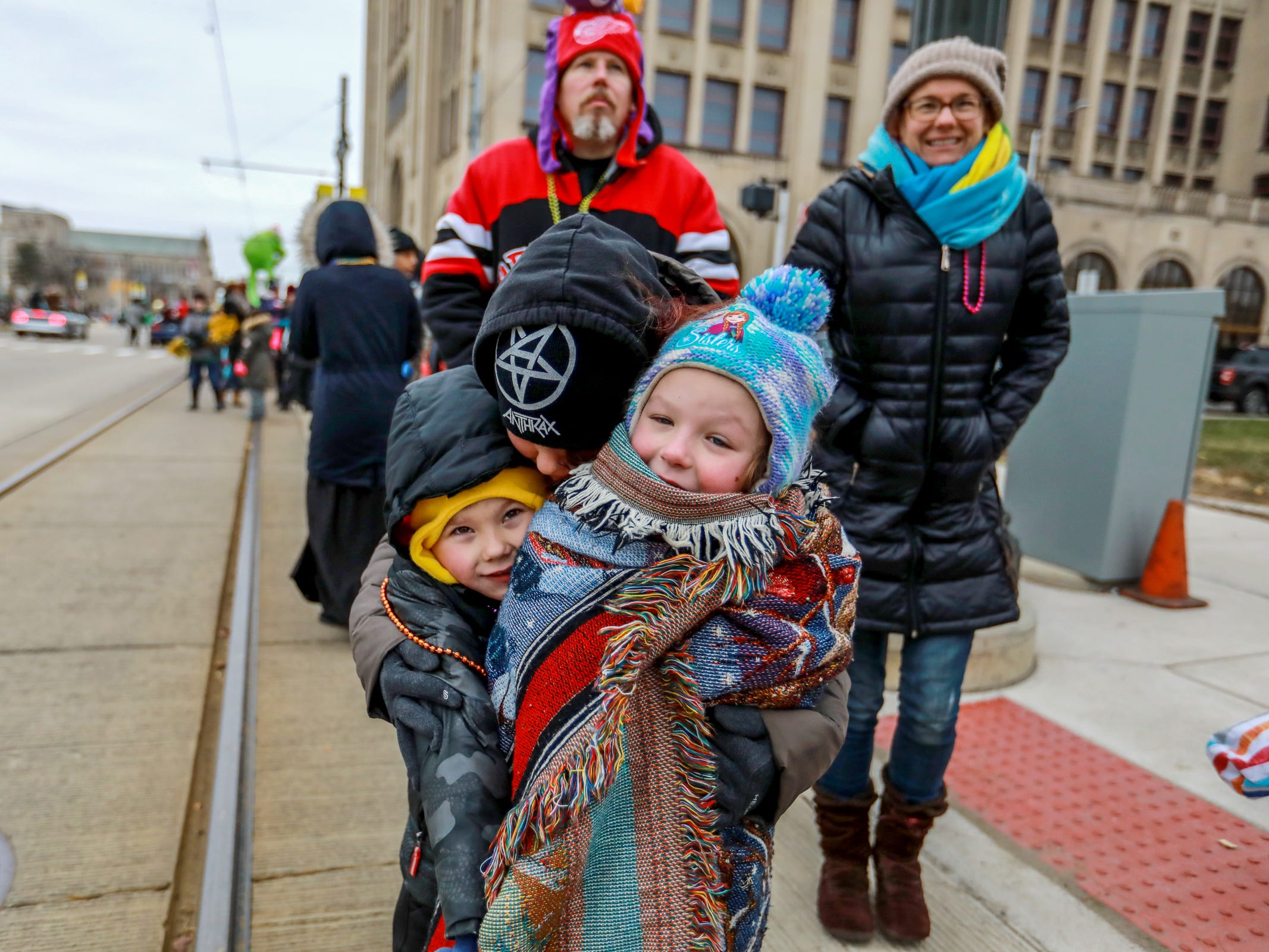 Christina Romero, 30, of East Pointe hugs Eric Pearsall, 5, left, and Aurora Cuthbertson, 6, of Mt. Clemens, Mich, as they stand on the side watching America's Thanksgiving Parade in Detroit on Thursday, Nov. 22, 2018.