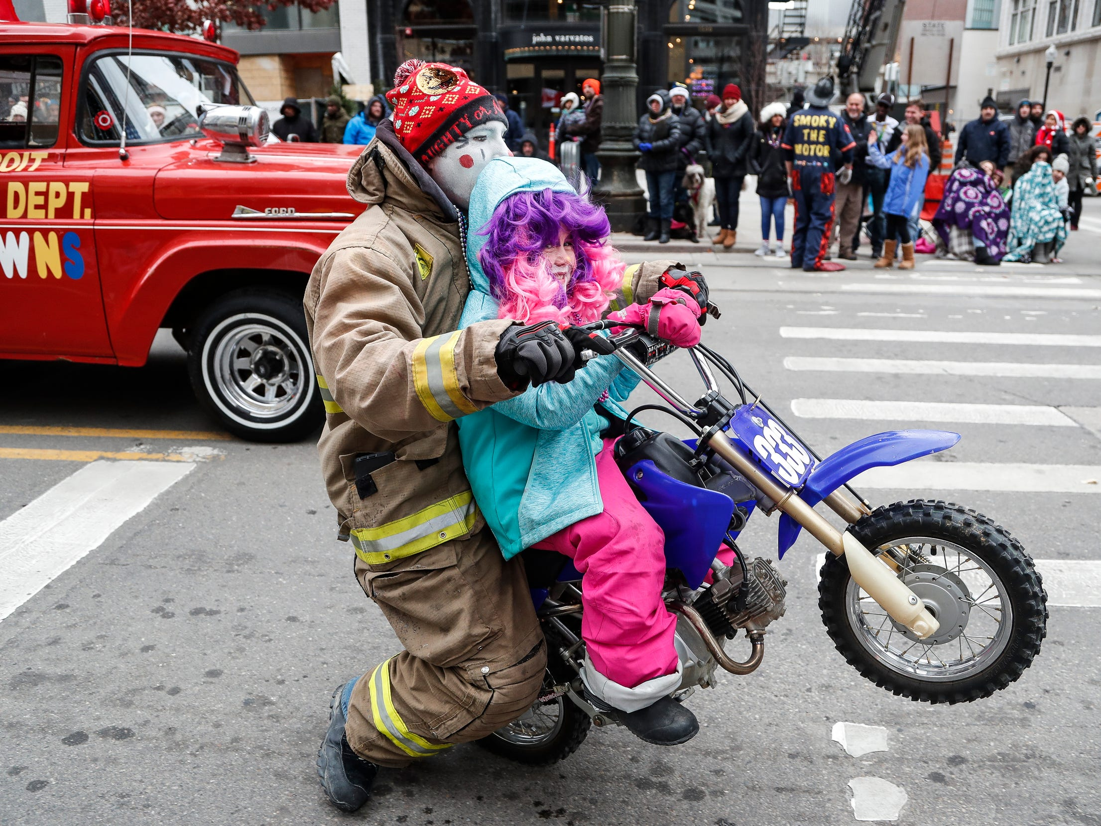 Detroit Fire Department clown Justin Parsons rides a motorcycle with Kinley Huff, 6, on Woodward Avenue during the 92nd America's Thanksgiving Day Parade in Detroit, Thursday, Nov. 22, 2018.