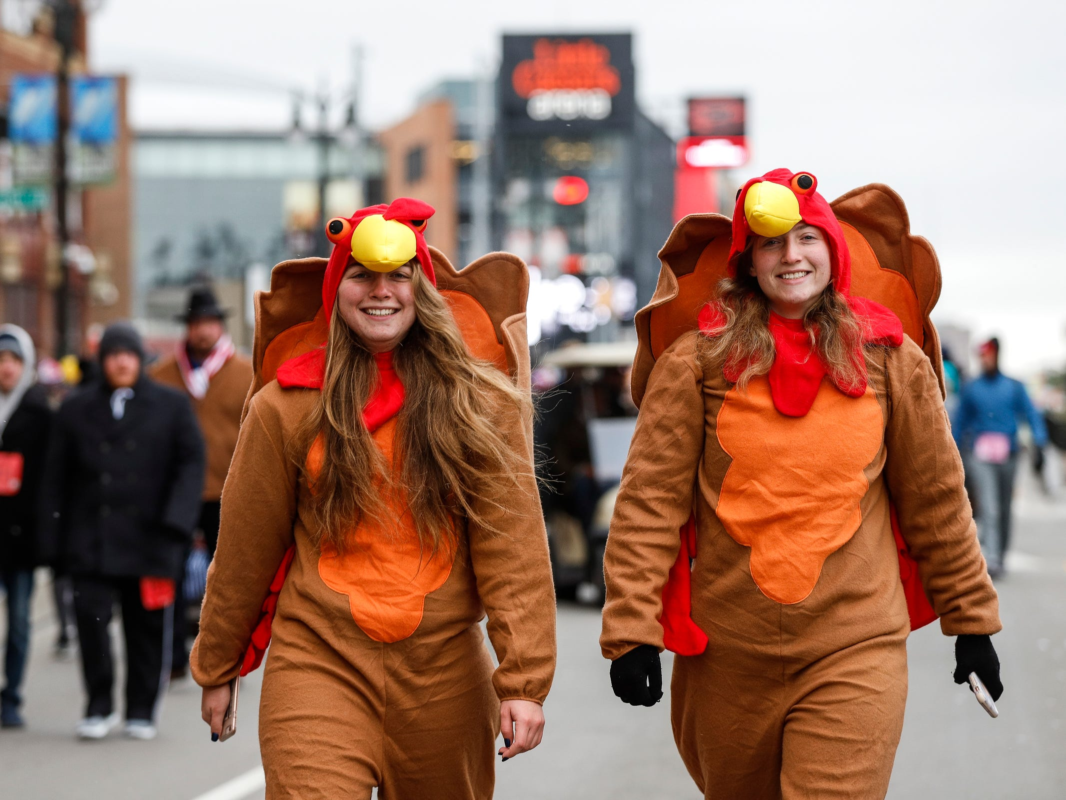 Emma Kelly, center, and her sister Devon Kelly, walks down Woodward Avenue during the Turkey Trot 5k and 10k in Detroit, Thursday, Nov. 22, 2018.