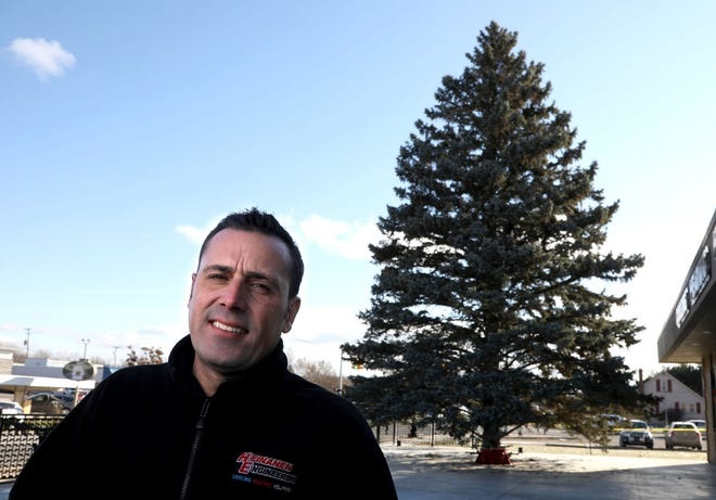 Jeff Heinanen, President of Heinanen Engineering in South Lyon, with a 53 foot Blue Spruce that he had installed in front of his business as the city's official Christmas tree. Jeff is photographed on Wednesday, Nov. 21, 2018.