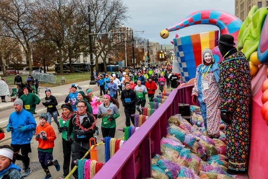 Runners participate in the Turkey Trot fun run before the start of America's Thanksgiving Parade presented by Art Van, while clowns Rosie Feinbloom, 17, of Bloomfield Hills and her father look on, in Detroit on Nov. 22, 2018.
