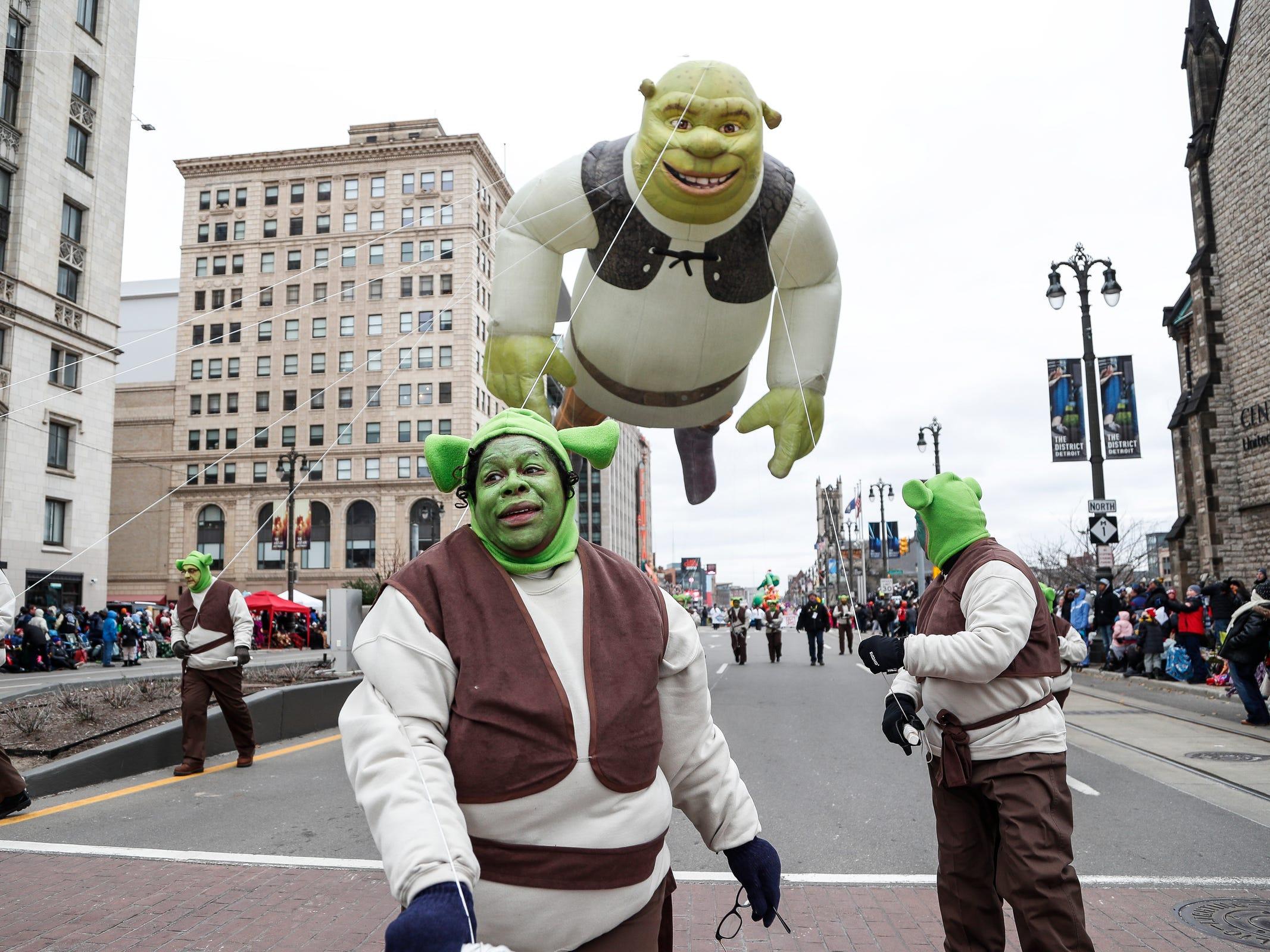 Shrek float handler Wendy Little, center, takes the balloon down Woodward Avenue during the 92nd America's Thanksgiving Day Parade in Detroit, Thursday, Nov. 22, 2018.